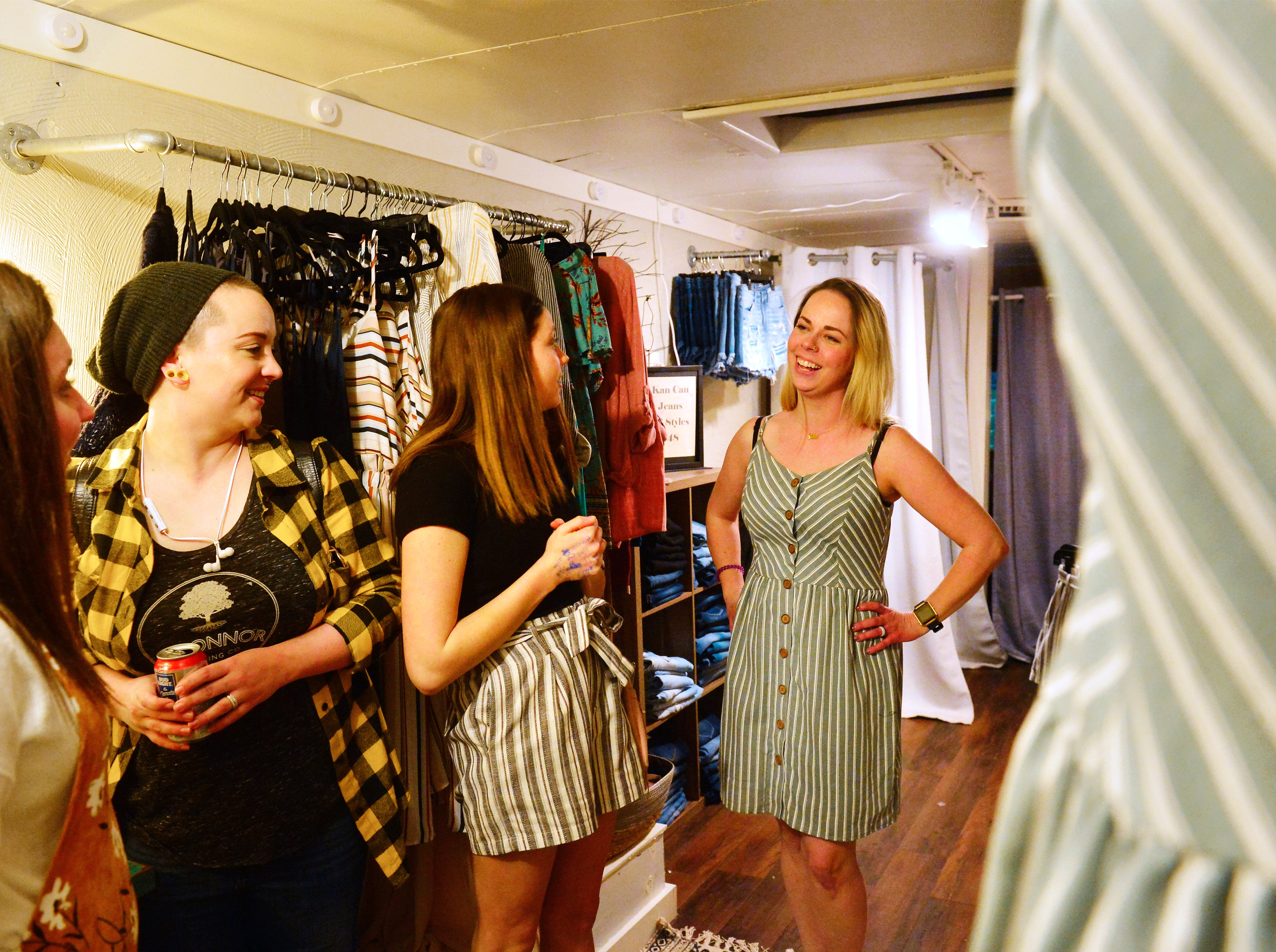 Caitlin Holmlund tries on a dress in the Dipity mobile boutique at the Great Western Living and Design Show in the Four Seasons Arena on Friday.