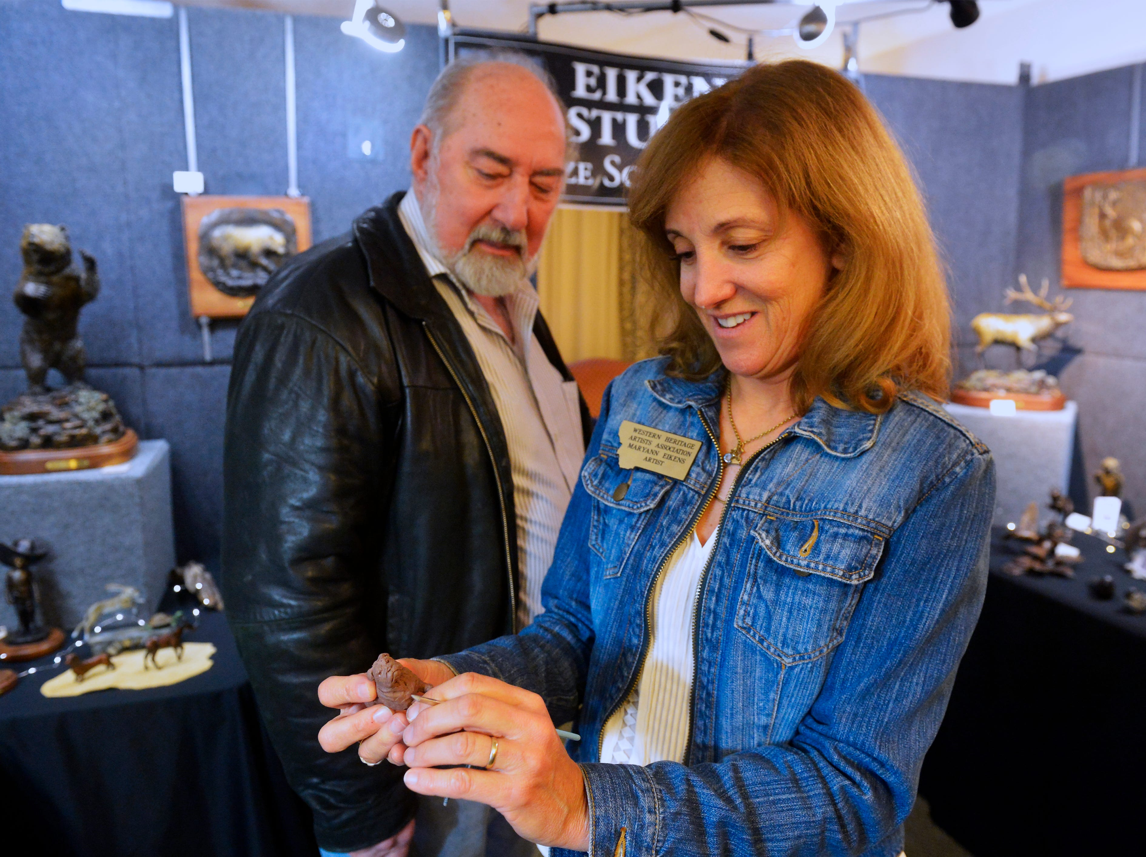 Sculptor Maryann Eikans talks with fellow artist Lyle Schwabauer in her room at the Western Heritage Artists Footprints on the Trail Art Show in the Holiday Inn, Friday.