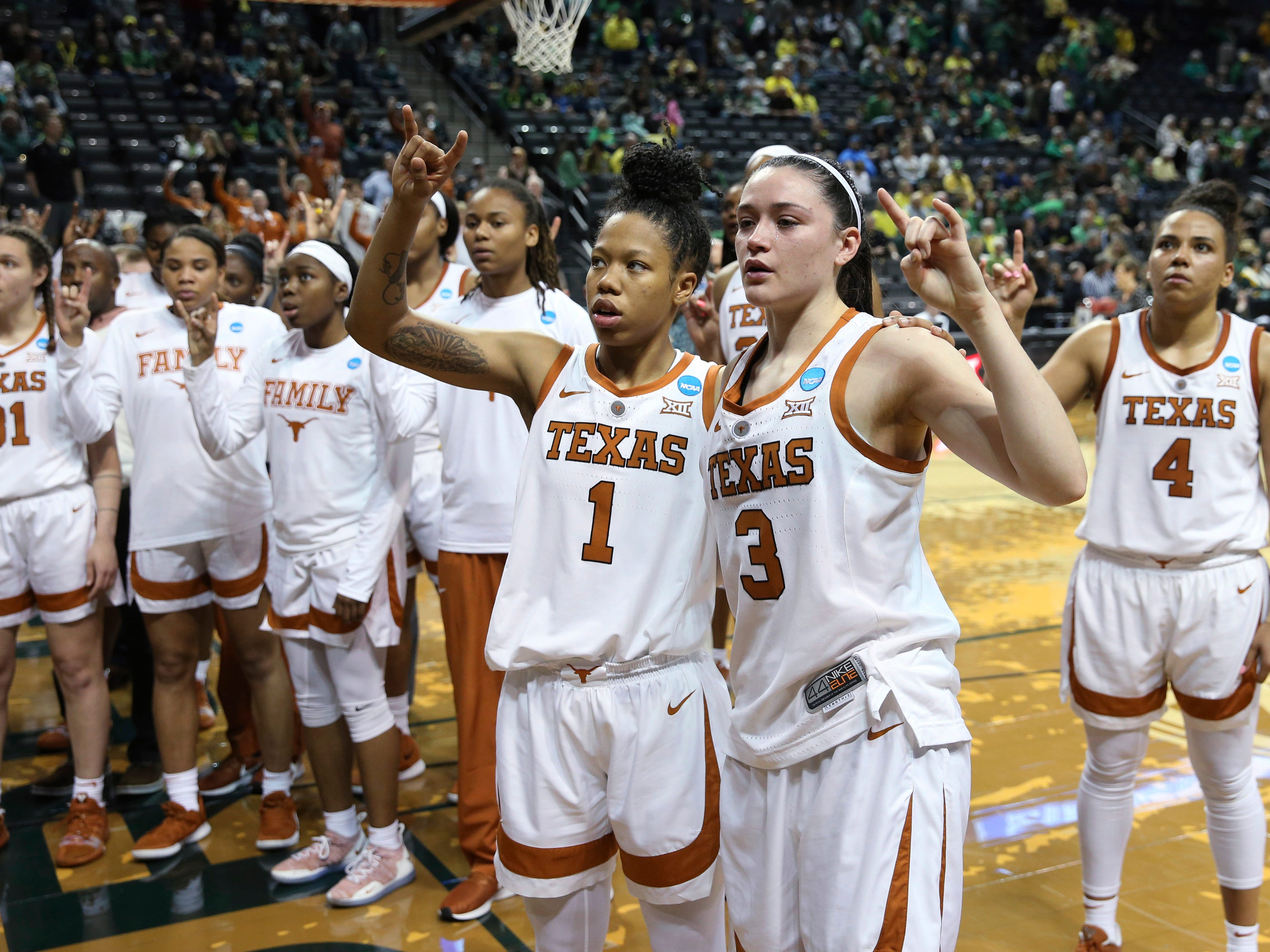 Texas players, including Sug Sutton, center left, and Danni Williams, center right, acknowledge fans after losing to Indiana in a first-round game of the NCAA women's college basketball tournament Friday, March 22, 2019, in Eugene, Ore.