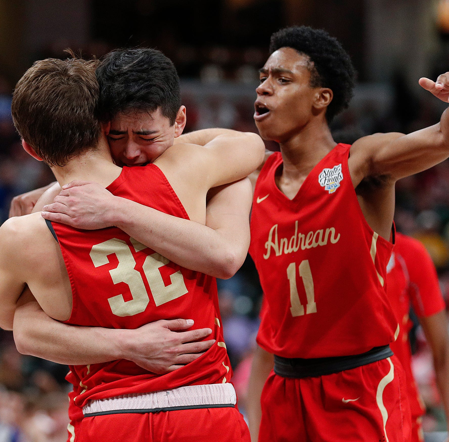 Andrean Fighting 59ers John Carrothers (4) hugs Nickolas Flesher (32) as Benjamin Jones (11) joins the celebration late in the second half of the IHSAA 2A Boys Basketball State Finals at Bankers Life Fieldhouse on Mar. 23, 2019. The Andrean Fighting 59ers defeated the Linton-Stockton Miners 59-54.