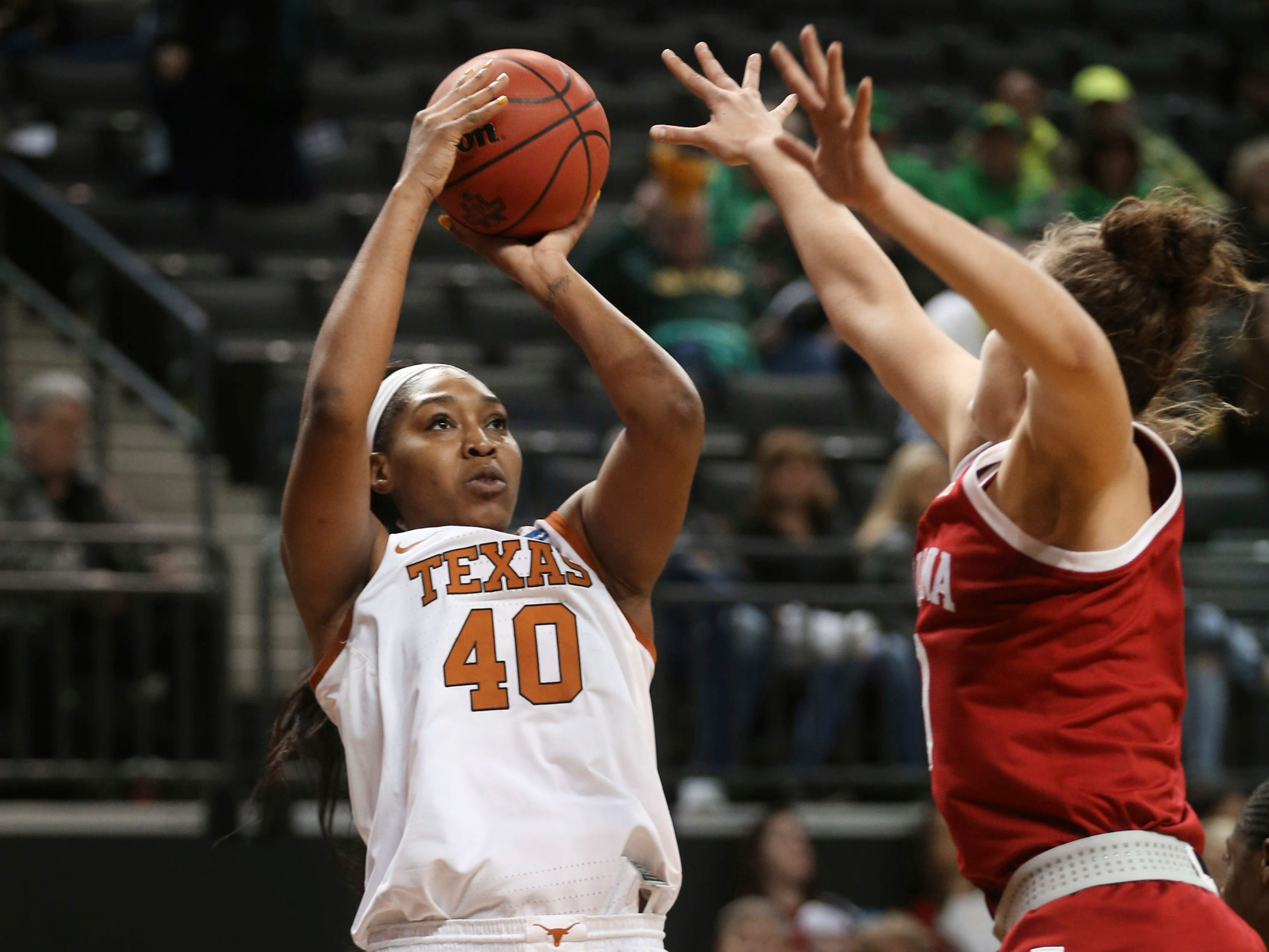 Texas' Jatarie White, left, shots over Indiana's Aleksa Gulbe during the first half of a first-round game in the NCAA women's college basketball tournament Friday, March 22, 2019, in Eugene, Ore. (AP Photo/Chris Pietsch)