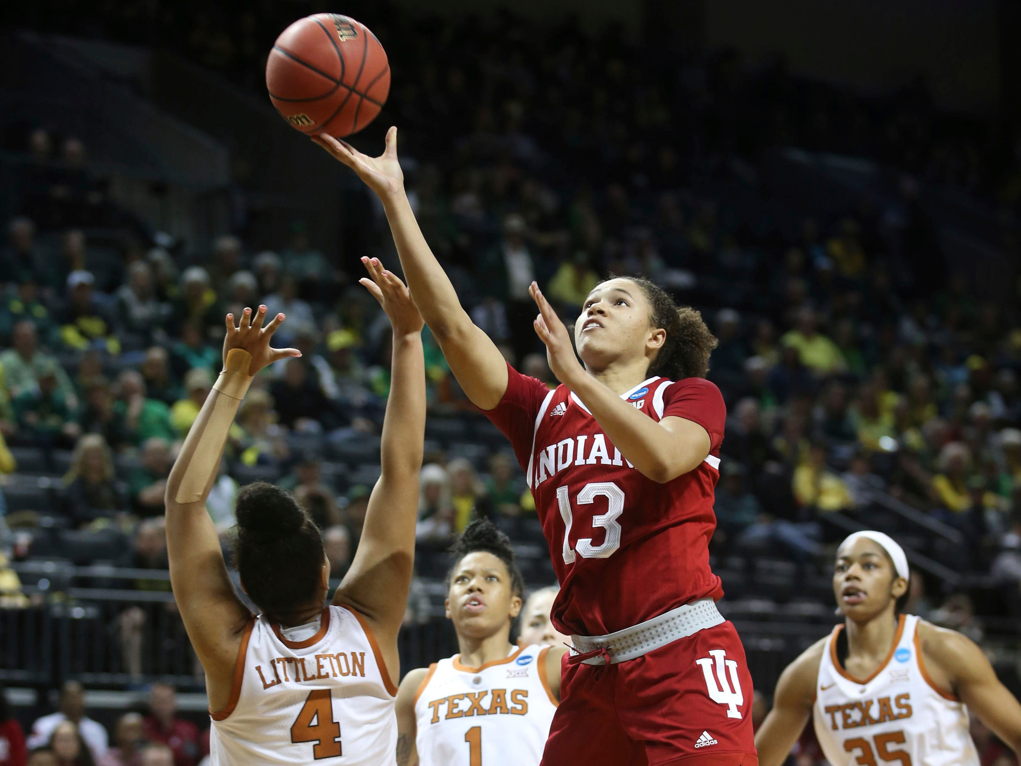 Indiana's Jaelynn Penn, center, shoots between Texas' Destiny Littleton, left, Sug Sutton and Charli Collier, right, during the second half of a first-round game in the NCAA women's college basketball tournament Friday, March 22, 2019, in Eugene, Ore.