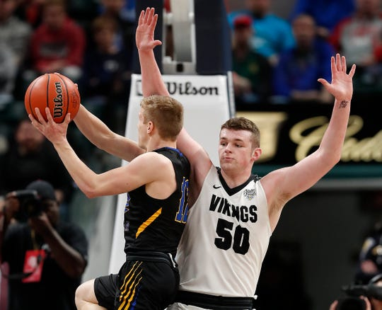Fort Wayne Blackhawk Christian Braves Michael Pulver (12) drives around Barr-Reeve Vikings Keegan O'Neil (50) in the first half of the IHSAA A Boys Basketball State Finals at Bankers Life Fieldhouse on Mar. 23, 2019.