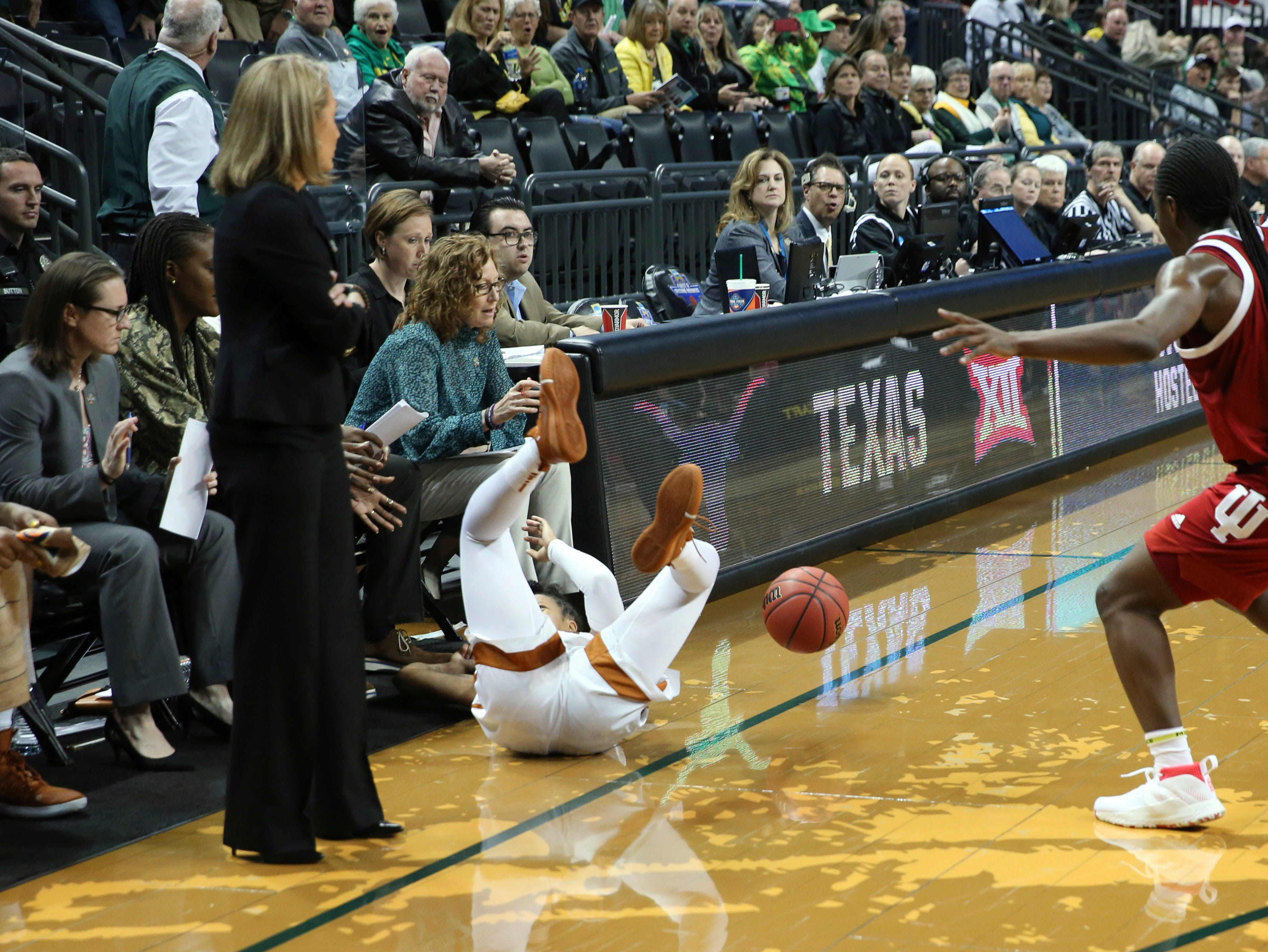 With Texas coach Karen Aston, left, watching, Texas' Sug Sutton, center, loses control of the ball under pressure from Indiana's Bendu Yeaney, right, at the end of a first-round game in the NCAA women's college basketball tournament Friday, March 22, 2019, in Eugene, Ore. (AP Photo/Chris Pietsch)
