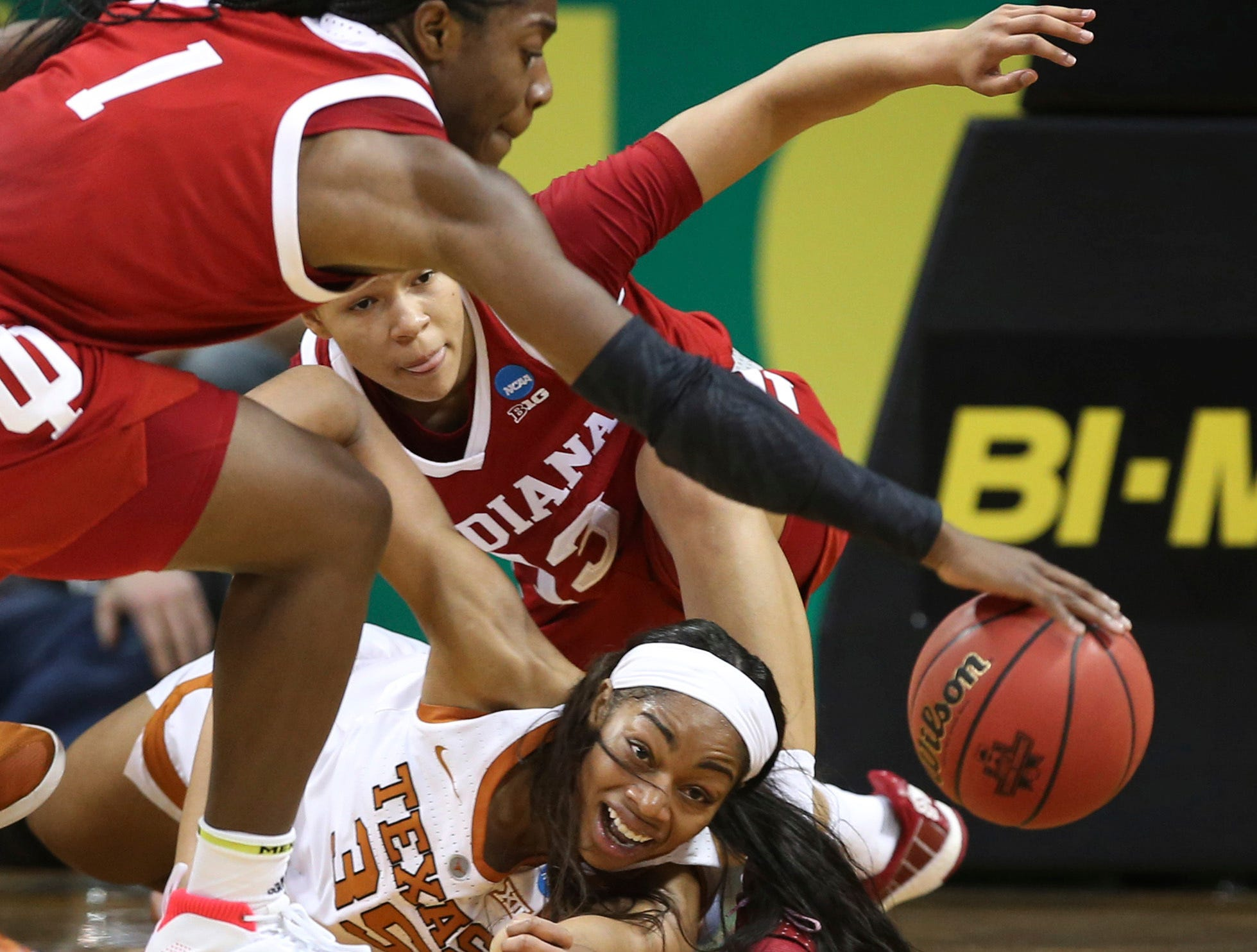 Indiana's Bendu Yeaney, left, comes up with a loose ball as teammate Jaelynn Penn, center, and Texas' Charli Collier, right, go to the floor during the second half of an NCAA women's college basketball tournament game Friday, March 22, 2019, in Eugene, Ore. (AP Photo/Chris Pietsch)