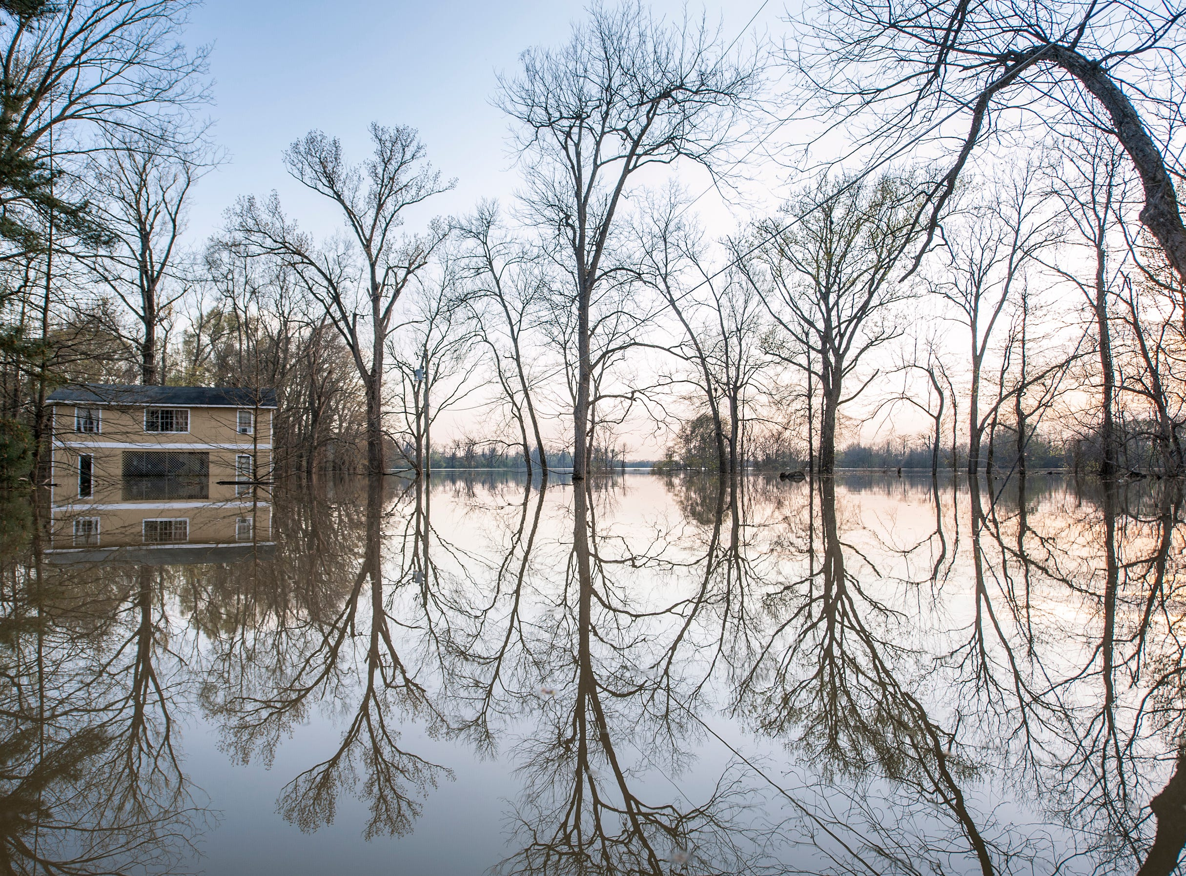 The sun begins to set on the waters of the overflowing Yazoo River filling the streets of the Chickasaw subdivision in Vicksburg, March 19, 2019.