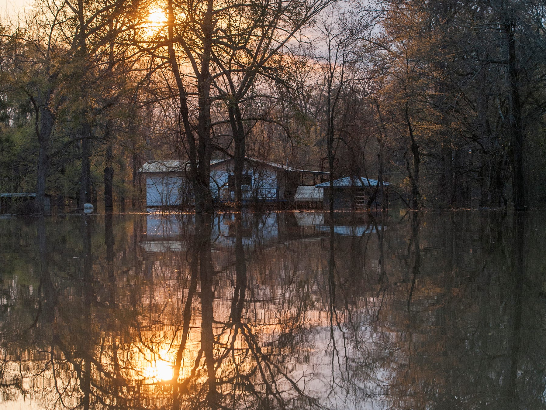 The sun sets on the waters of the overflowing Yazoo River filling the streets of the Chickasaw subdivision in Vicksburg on March 19, 2019.