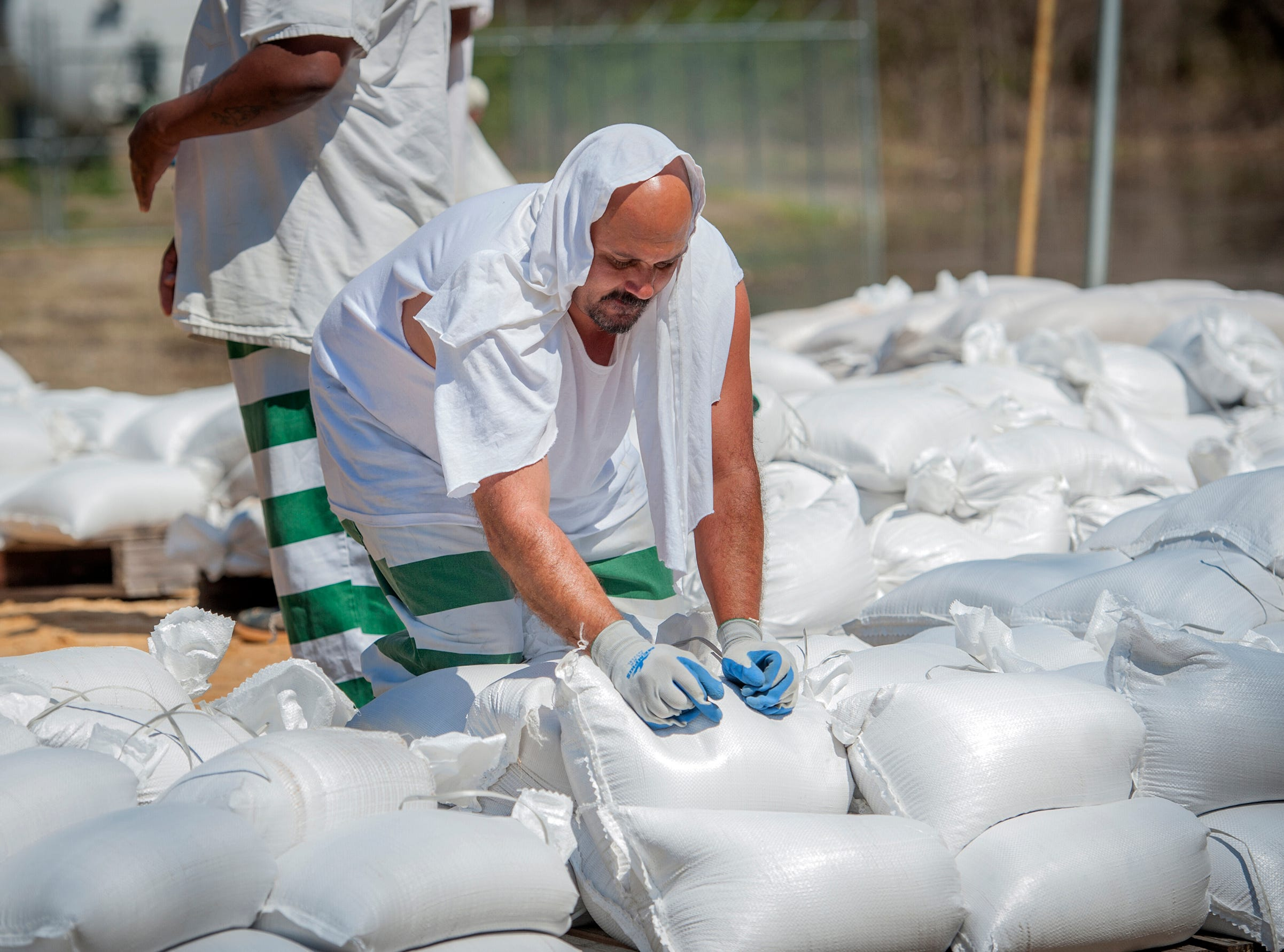A state inmate, residing in the Issaquena County Correctional Facility, fills sandbags to help battle flooding in the county.