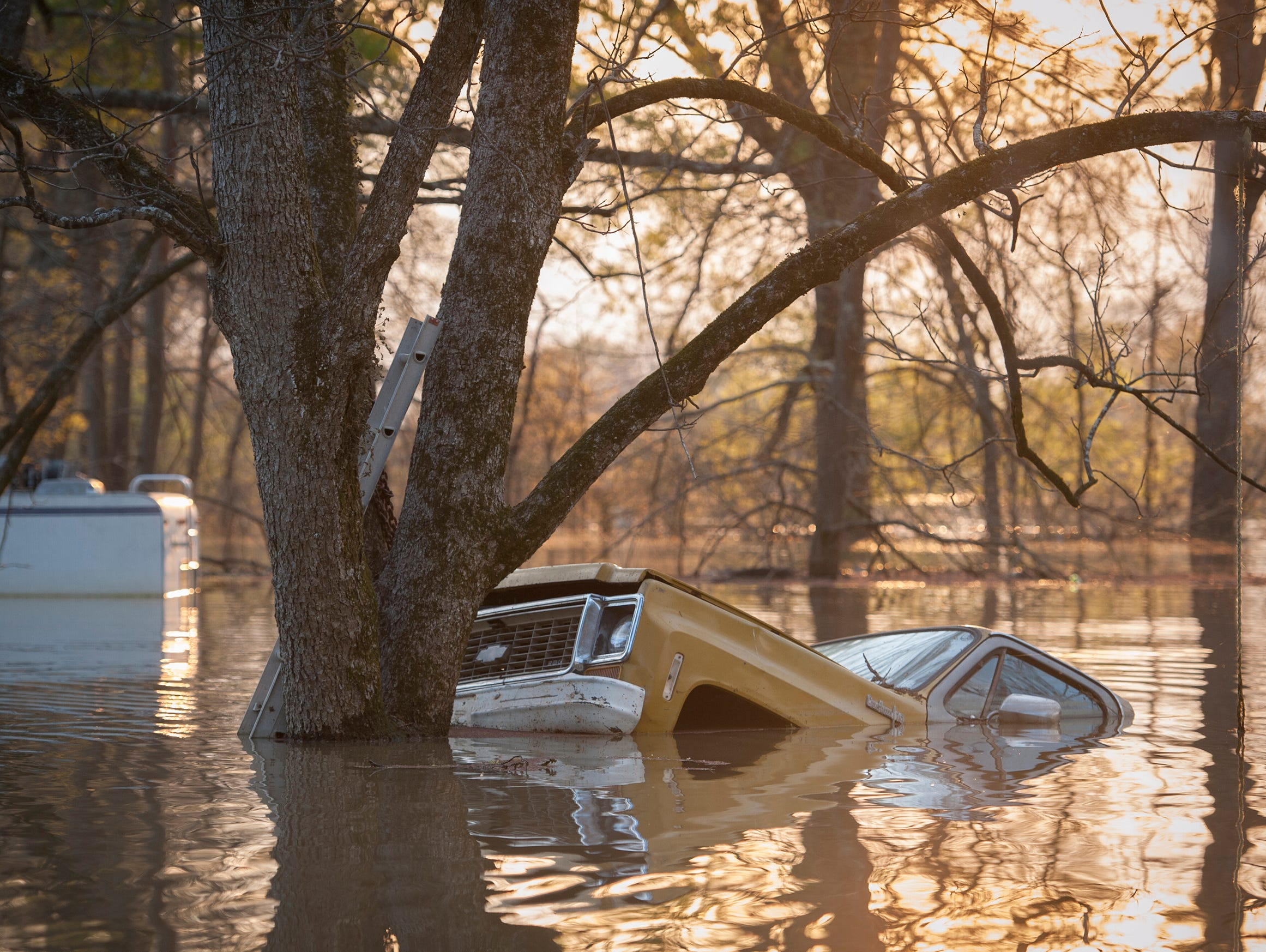 The sun sets on flooding in the Chickasaw subdivision in Vicksburg, March 19, 2019.