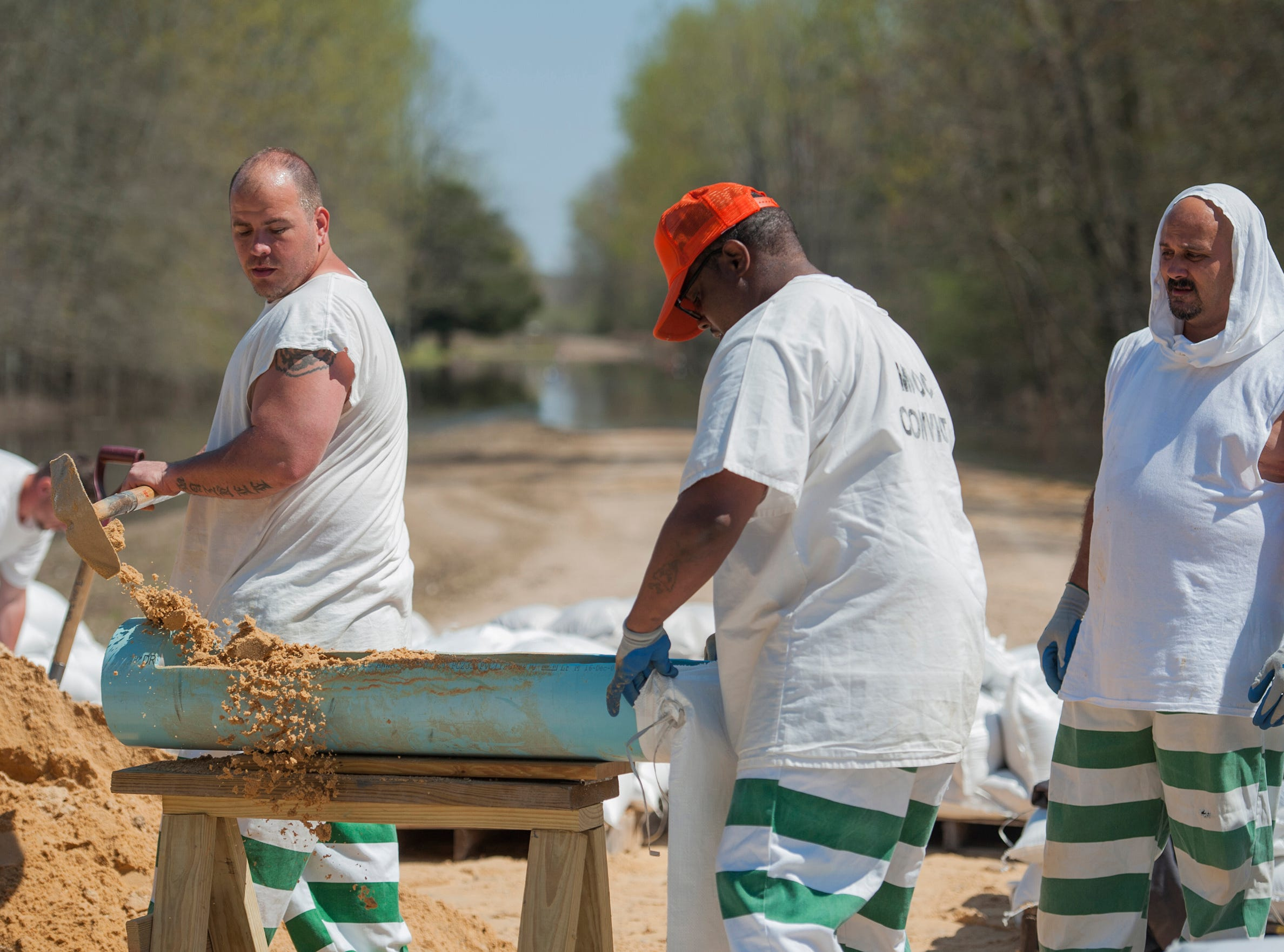 State inmates, residing in the Issaquena County Correctional Facility, fill sandbags to help battle flooding in the county.