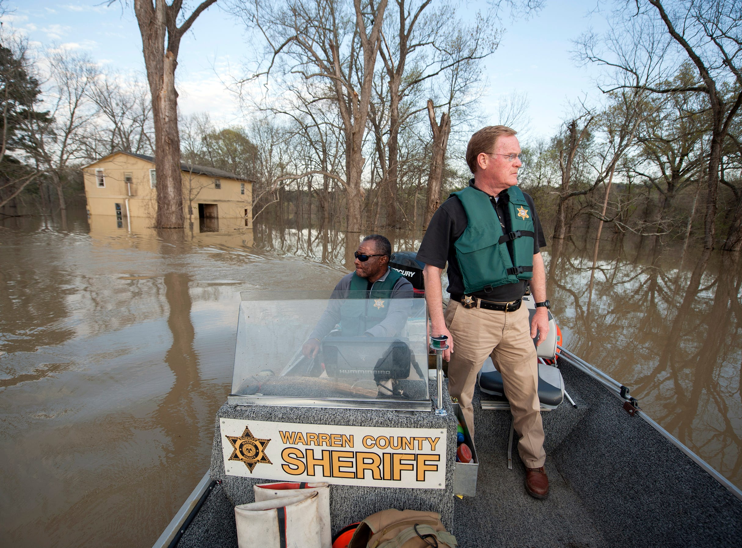Warren County Sheriff Martin Pace, standing, and Det. Sam Winchester, move slowly through the Chickasaw subdivision in Vicksburg, flooded by the Yazoo River. Hit hard by river flooding in previous years, many people have long abandoned their homes. Some, who had chosen to stay have either evacuated for this flood or are making do, traveling in and out by boat.