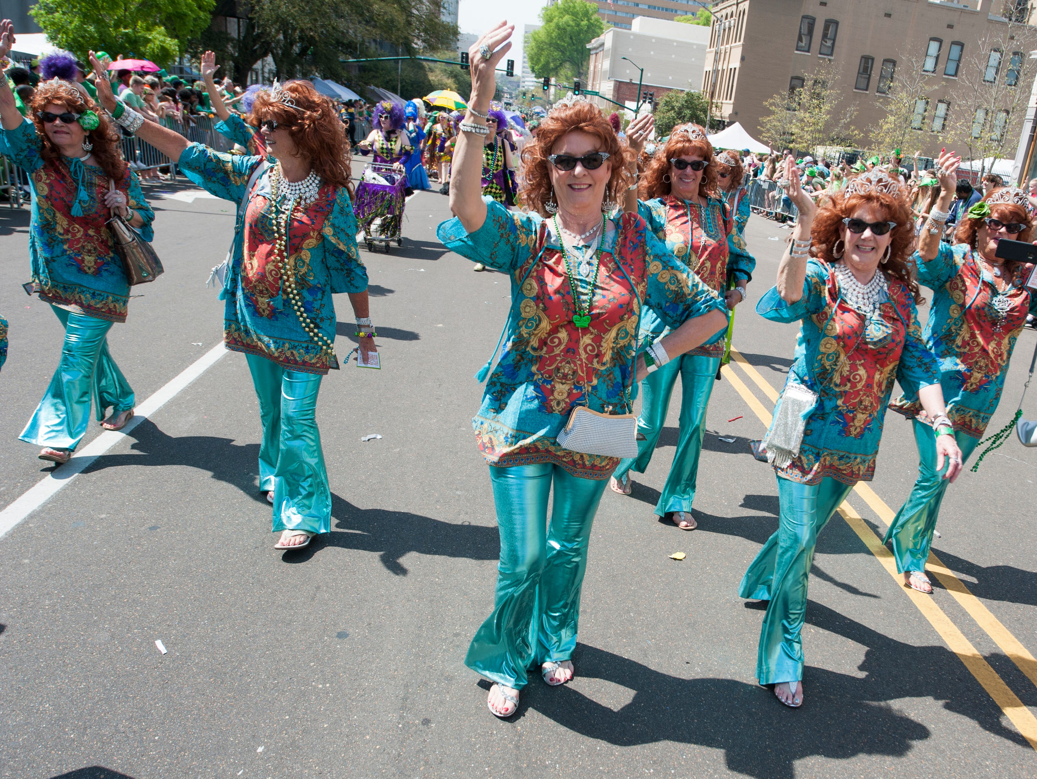 Sweet Potato wannabes from The Villages in Florida have perfected their royal wave for their march in Hal's St. Paddy's Day Parade, Saturday, March 23, 2019.