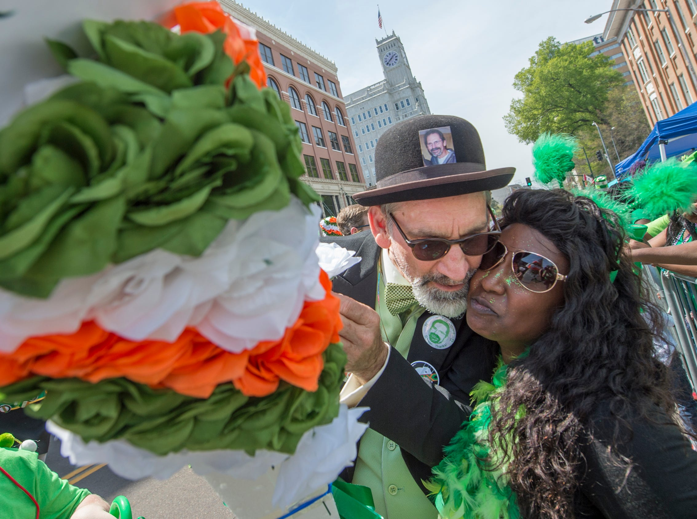 With a photo of his brother, Hal White, tucked firmly in the bond of his derby, Malcolm White gives a flower to Niki Thompson Shearry of Jackson and gets a hug and kiss in return during Hal's St. Paddy's Day Parade Saturday, March 23, 2019. Hal White is the namesake of the parade.