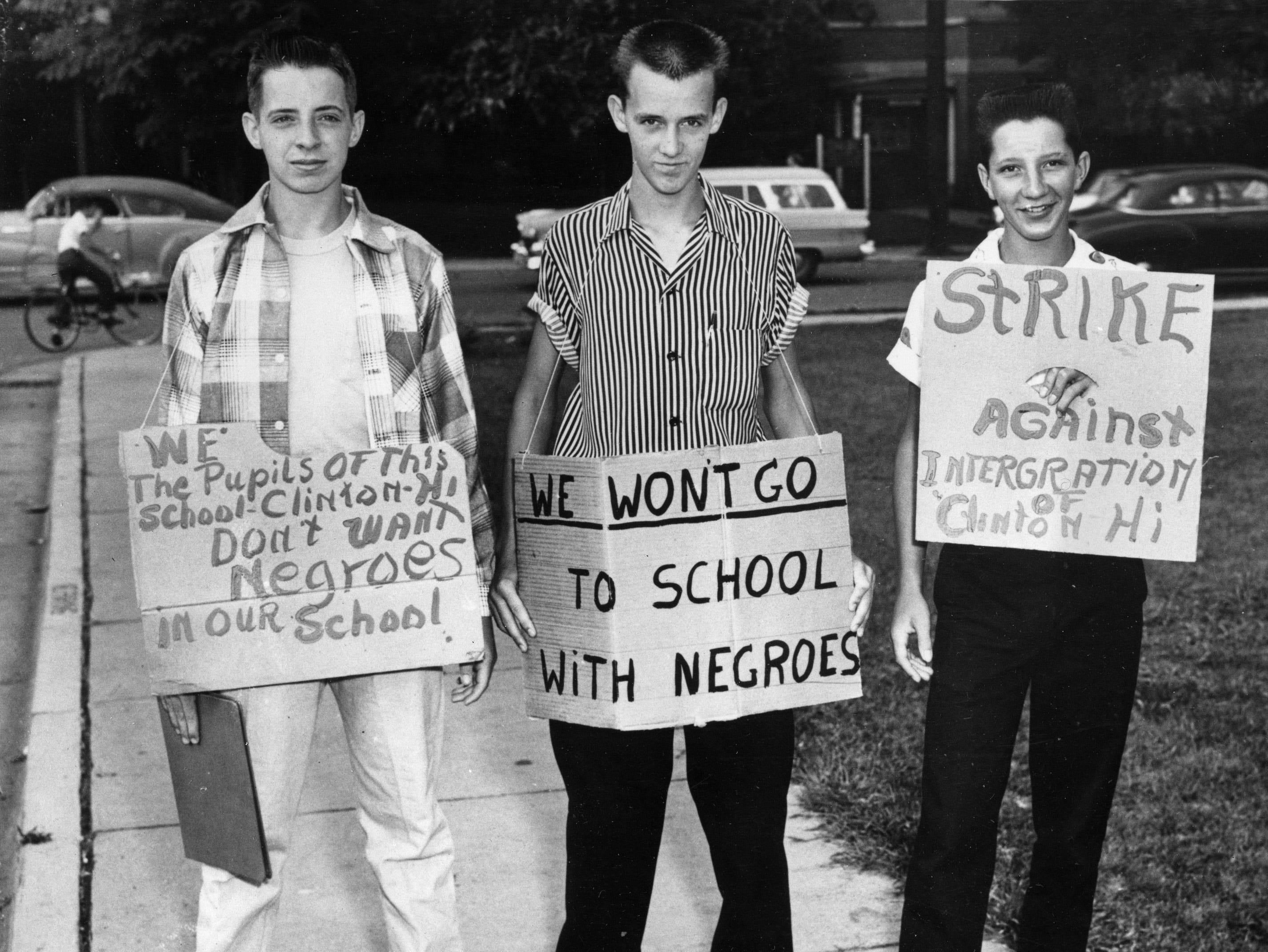 Three students at Clinton High School picket their school as it became the first state-supported school in Tennessee to integrate, Aug. 27, 1956.  The boys are, from left, Buddy Trammell, Max Stiles and Tommy Sanders.  Trammell and Sanders later discarded the pro-segregation signs and reported to classes.  (AP Photo)