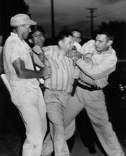 It took several officers to restrain Thomas B. Miller, center, 33, of Rockwood, as he was led to jail at Clinton on charges of disorderly conduct and resisting arrest. Dated: Sep. 1, 1956.