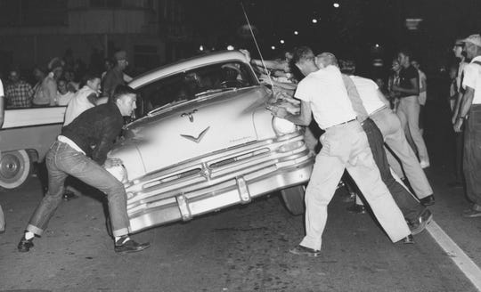 An angry mob tries to overturn a car carrying blacks passing through Clinton, Tenn., in a file photo from Aug. 31, 1956. The driver sped away before the doors were opened. The mob was motivated by the start of court-ordered desegregation three days earlier at Clinton High School. (AP Photo/Gene Herrick)