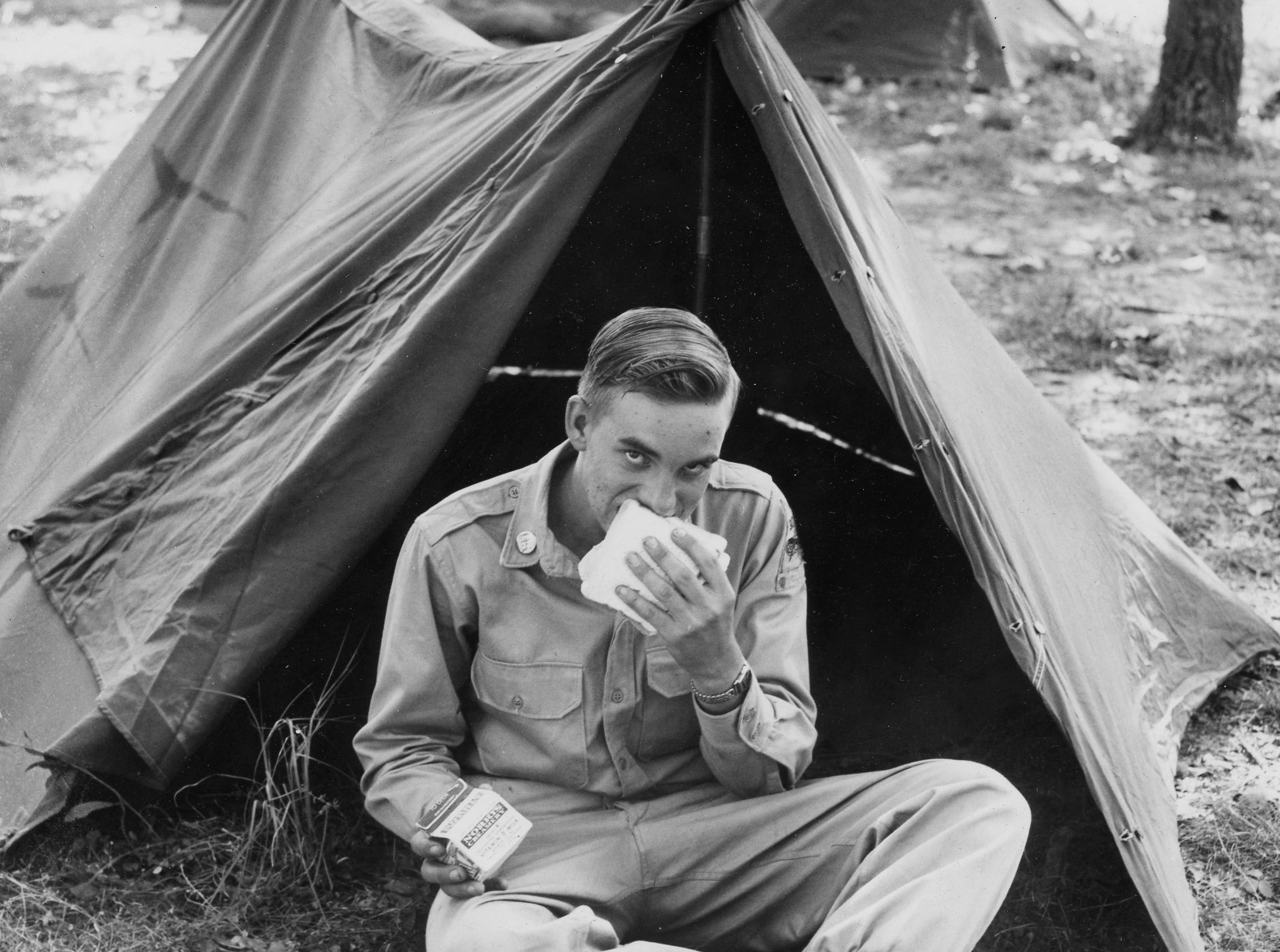 Pvt. Frank Smith of Crossville, member of Tennessee National Guard Company D 230th Recon Battalion, takes time out to eat choe in from of his tent at Clinton. Dated: Sept. 4, 1956.