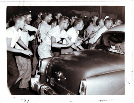 Angry protesters surround a black motorist's car in downtown Clinton during the unrest that accompanied desegregation of Clinton High School. 08/01/1956. Photo from Knoxville News Sentinel archive.