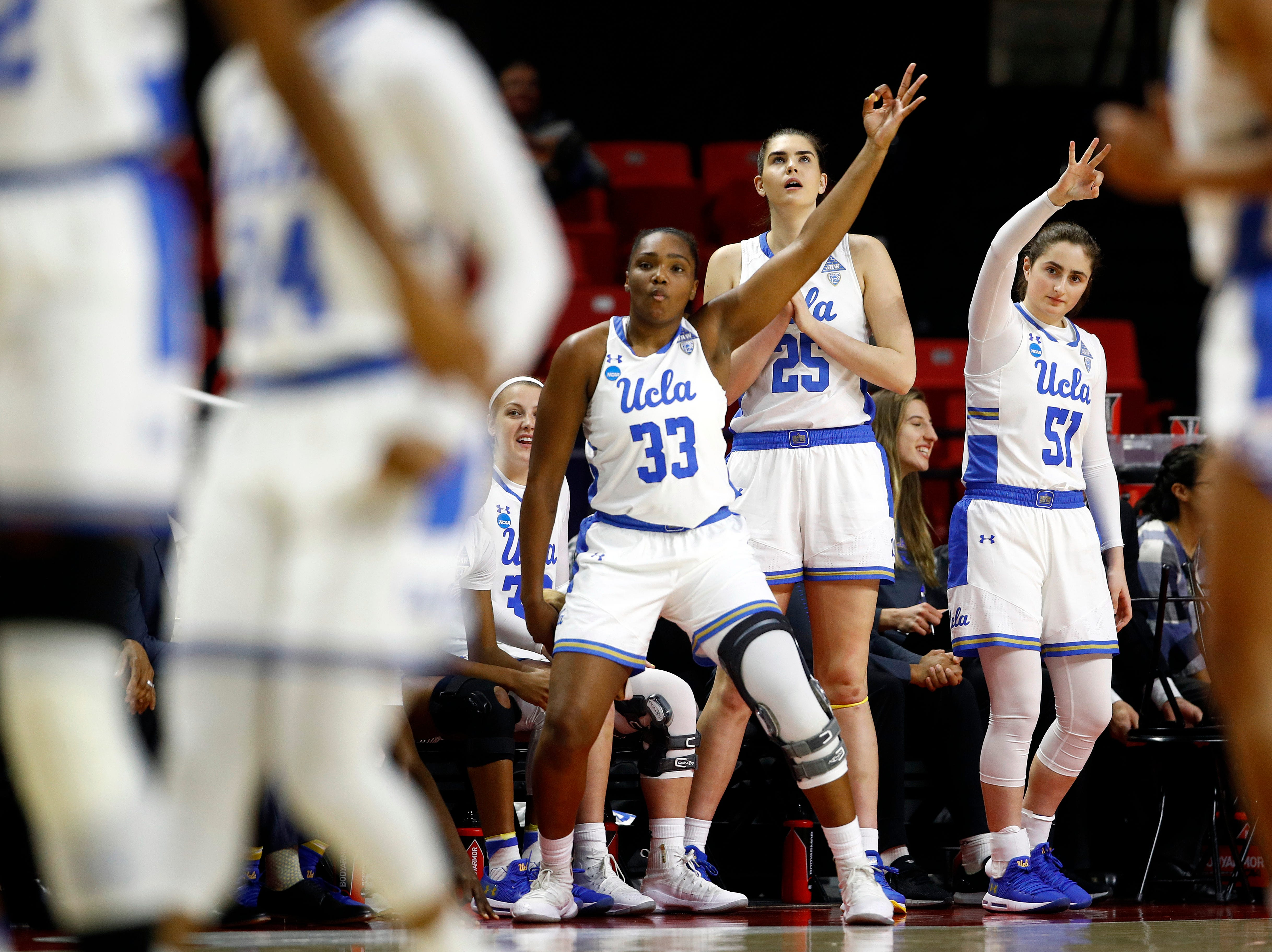 UCLA's Lauryn Miller (33), Shayley Harris (25) and Eliana Sigal (51) gesture after teammate Japreece Dean scored a 3-pointer in the first half of a first-round game against Tennessee in the NCAA women's college basketball tournament, Saturday, March 23, 2019, in College Park, Md.