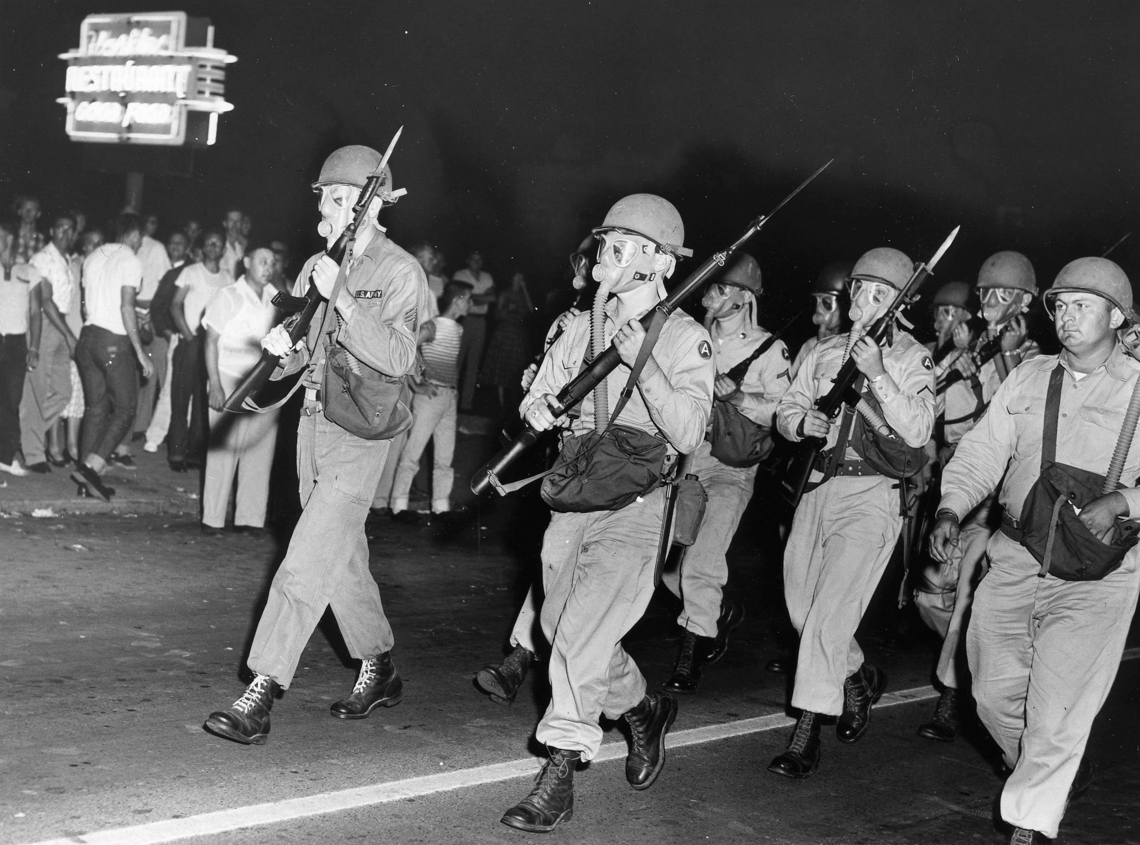 Tennessee National Guardsmen, wearing gas masks march with fixed bayonets into the courthouse square to clear the streets of demonstrators and prevent another riot from taking place in Clinton. Dated: Sep. 3, 1956.