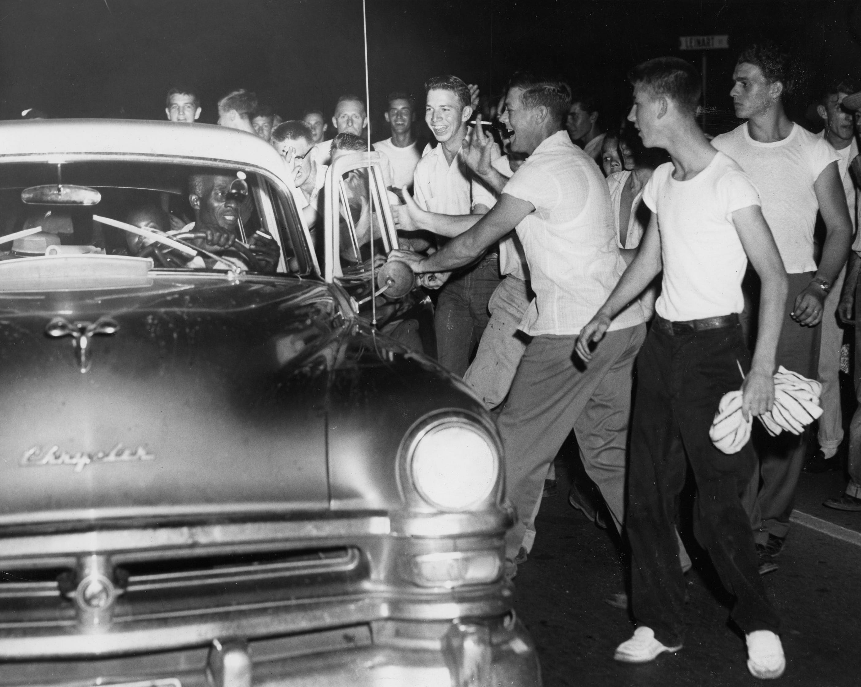 The mob descends on an Ohio car, its first, last night. The driver kept smiling despite the jostling he and the other occupants received before he succeeded in speeding away. Dated: Sept. 1, 1956.
