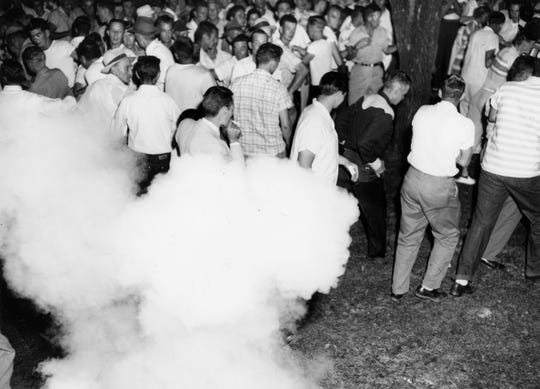 Tear gas bombs thrown by police cause rioters to disperse durint the integration riots in Clinton. Dated: Sept. 1, 1956.