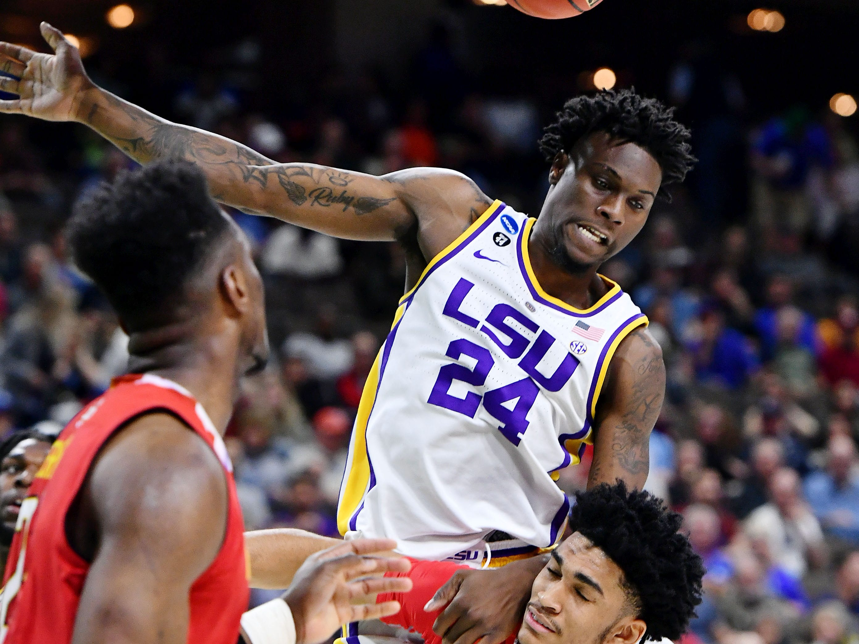 Mar 23, 2019; Jacksonville, FL, USA; LSU Tigers forward Emmitt Williams (24) lands on Maryland Terrapins forward Ricky Lindo Jr. (14) after making a basket during the first half in the second round of the 2019 NCAA Tournament at Jacksonville Veterans Memorial Arena. Mandatory Credit: John David Mercer-USA TODAY Sports