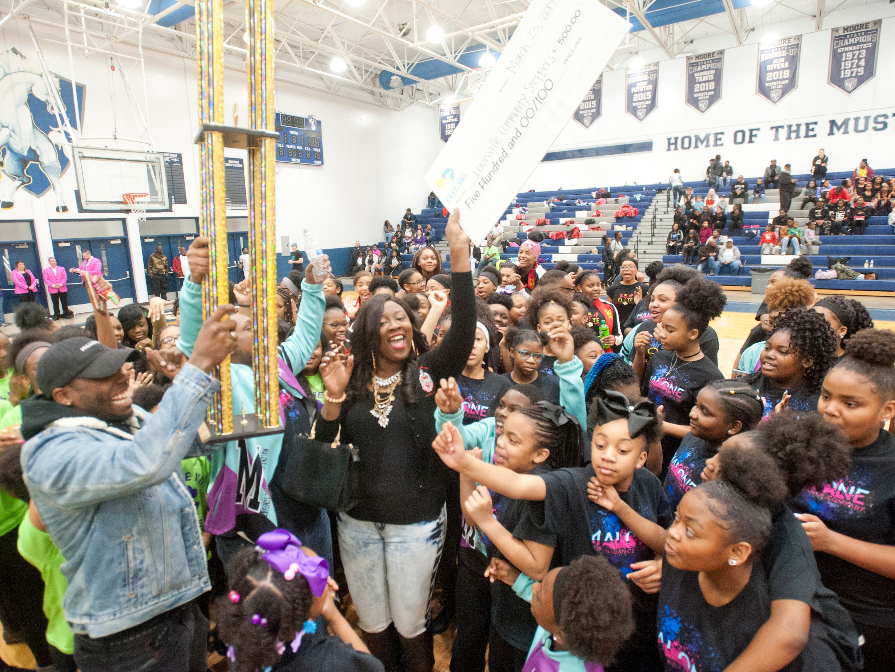 Jasmine Collins, center, coach of KY Elite, part of the combined Louisville Community Stepper, holds up a check for $500 as the group took 1st place in the StepFest community category during the Kentucky Derby Festival event sponsored by Louisville Parks and Recreation and held at Moore Traditional High School. 23 March 2019