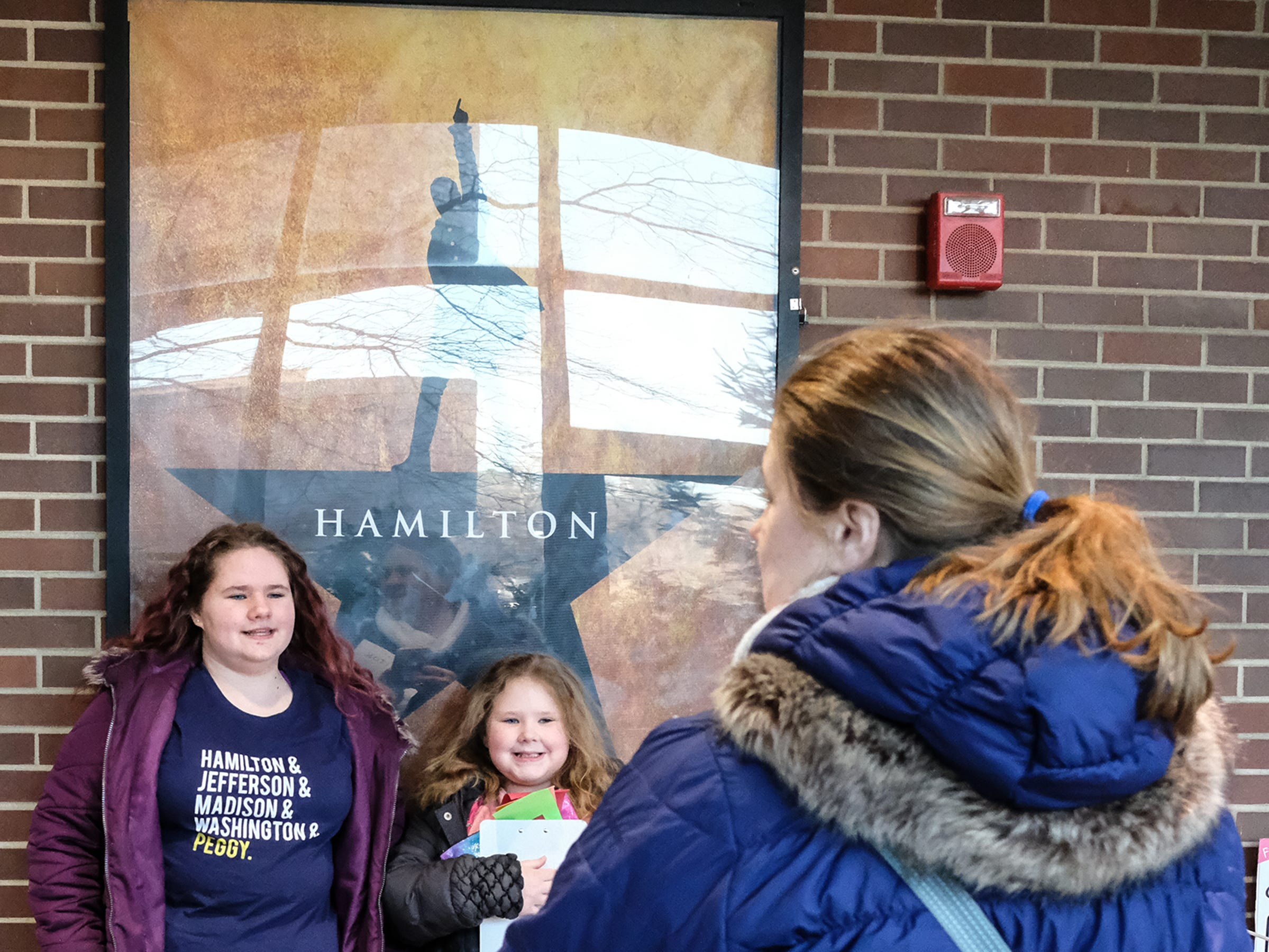 """Coming from St. Clair Shores, the McCoy family, Riley, 13, Cecilia, 7, and their mom Nicole pose for photos at the Wharton Center Saturday, March 23, 2019, as they continue their quest for tickets to """"Hamilton."""""""