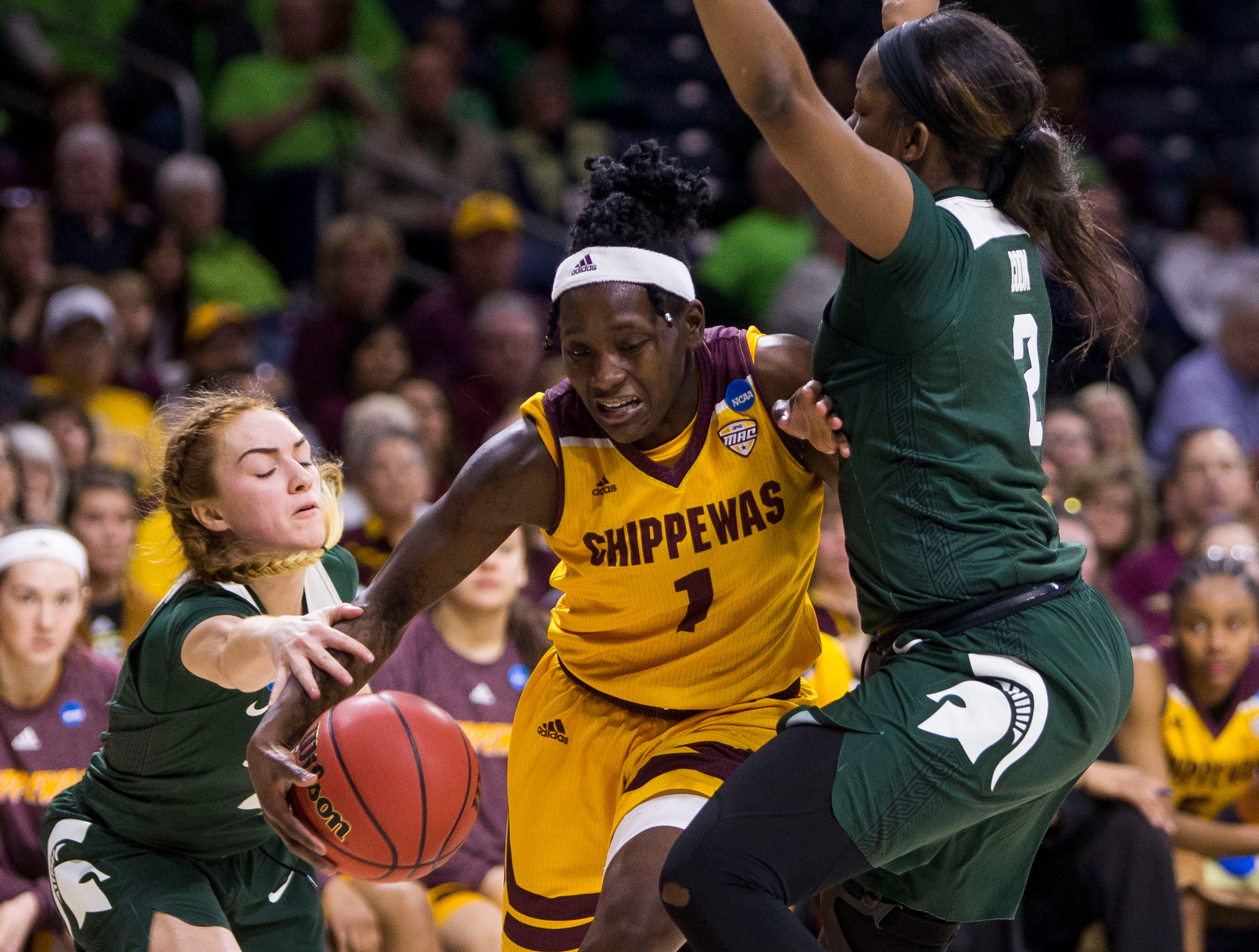 Central Michigan's Micaela Kelly (1) tries to drive between Michigan State's Taryn McCutcheon, left, and Mardrekia Cook during a first-round game in the NCAA women's college basketball tournament in South Bend, Ind., Saturday, March 23, 2019. Michigan State won 88-87.