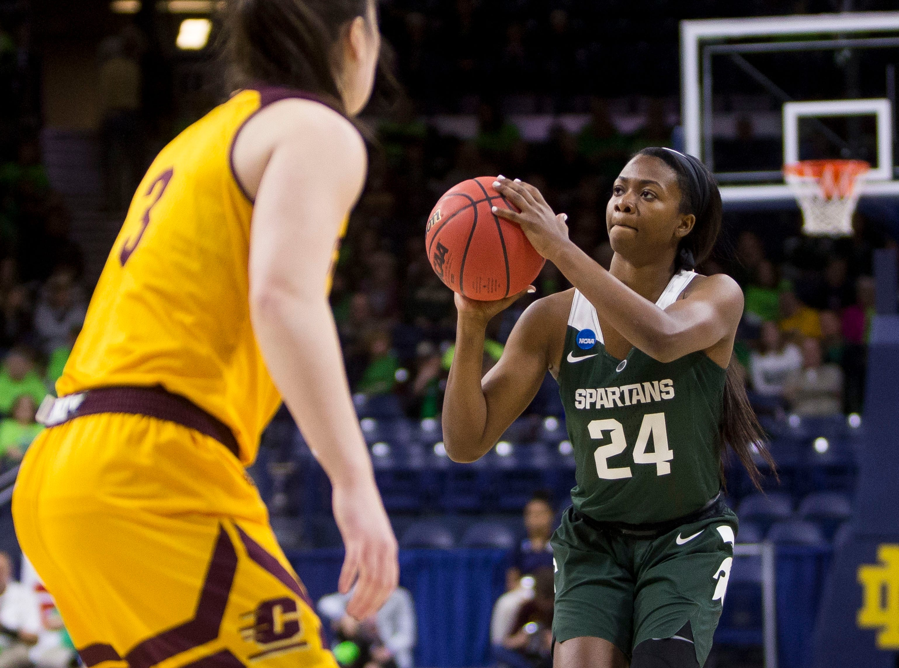 Michigan State's Nia Clouden (24) goes up for a 3-pointer in front of Central Michigan's Presley Hudson (3) during a first-round game in the NCAA women's college basketball tournament in South Bend, Ind., Saturday, March 23, 2019. (AP Photo/Robert Franklin)