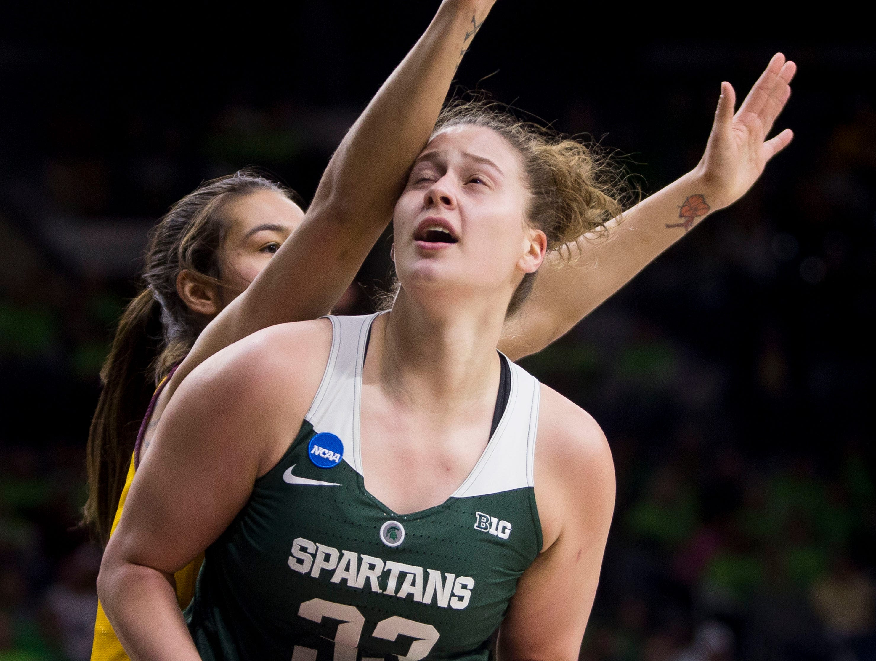Michigan State's Jenna Allen (33) looks for a shot with pressure from Central Michigan's Reyna Frost during a first-round game in the NCAA women's college basketball tournament in South Bend, Indiana, Saturday, March 23, 2019.