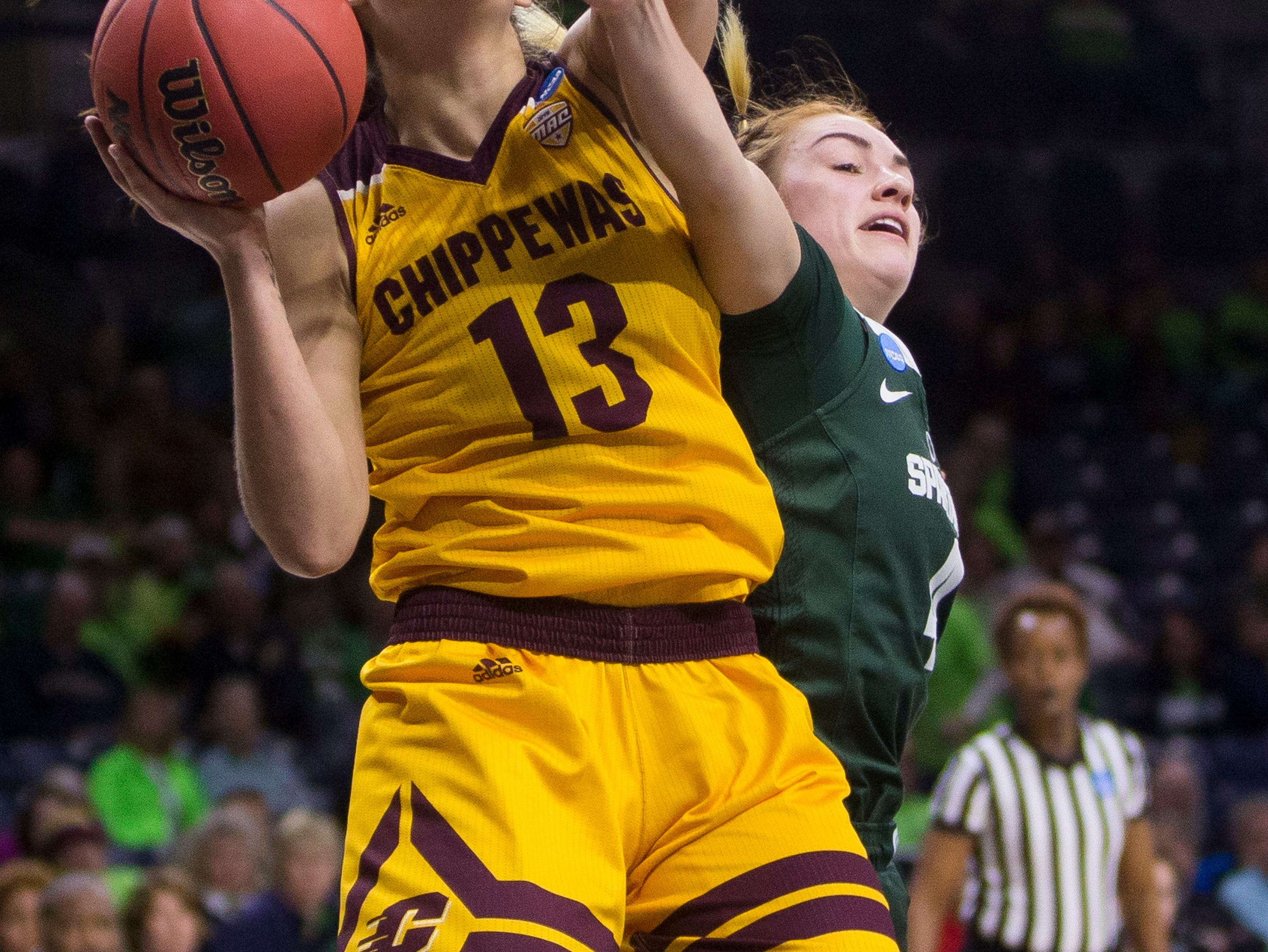 Central Michigan's Reyna Frost (13) goes up for a shot as Michigan State's Taryn McCutcheon defends during a first-round game in the NCAA women's college basketball tournament in South Bend, Ind., Saturday, March 23, 2019. (AP Photo/Robert Franklin)