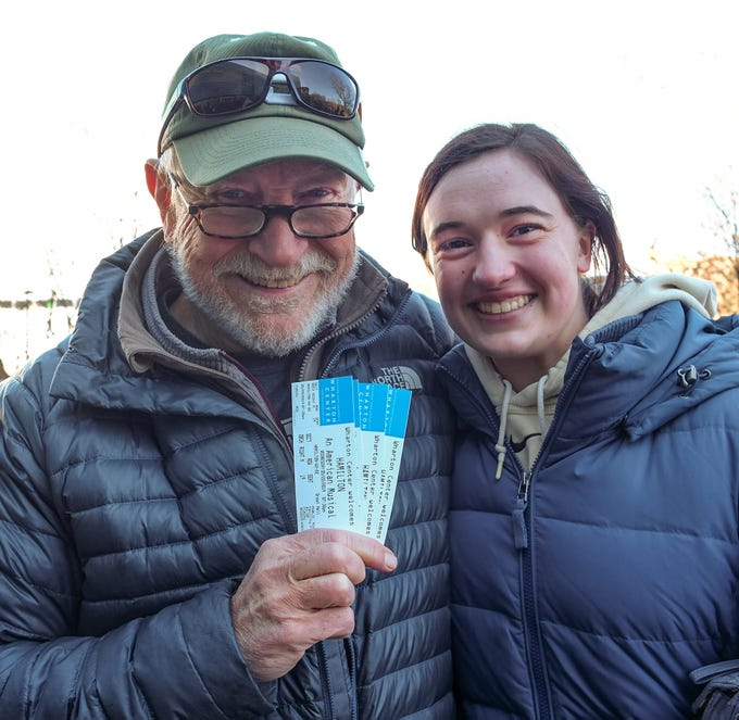 """Norm Sauer and granddaughter and MSU student Ellie Weise are all smiles as they were lucky to secure """"Hamilton"""" tickets as they went on sale at the Wharton Center Saturday, March 23, 2019. They arrived at 7 a.m. in the cold to stand in line for the chance to get them."""