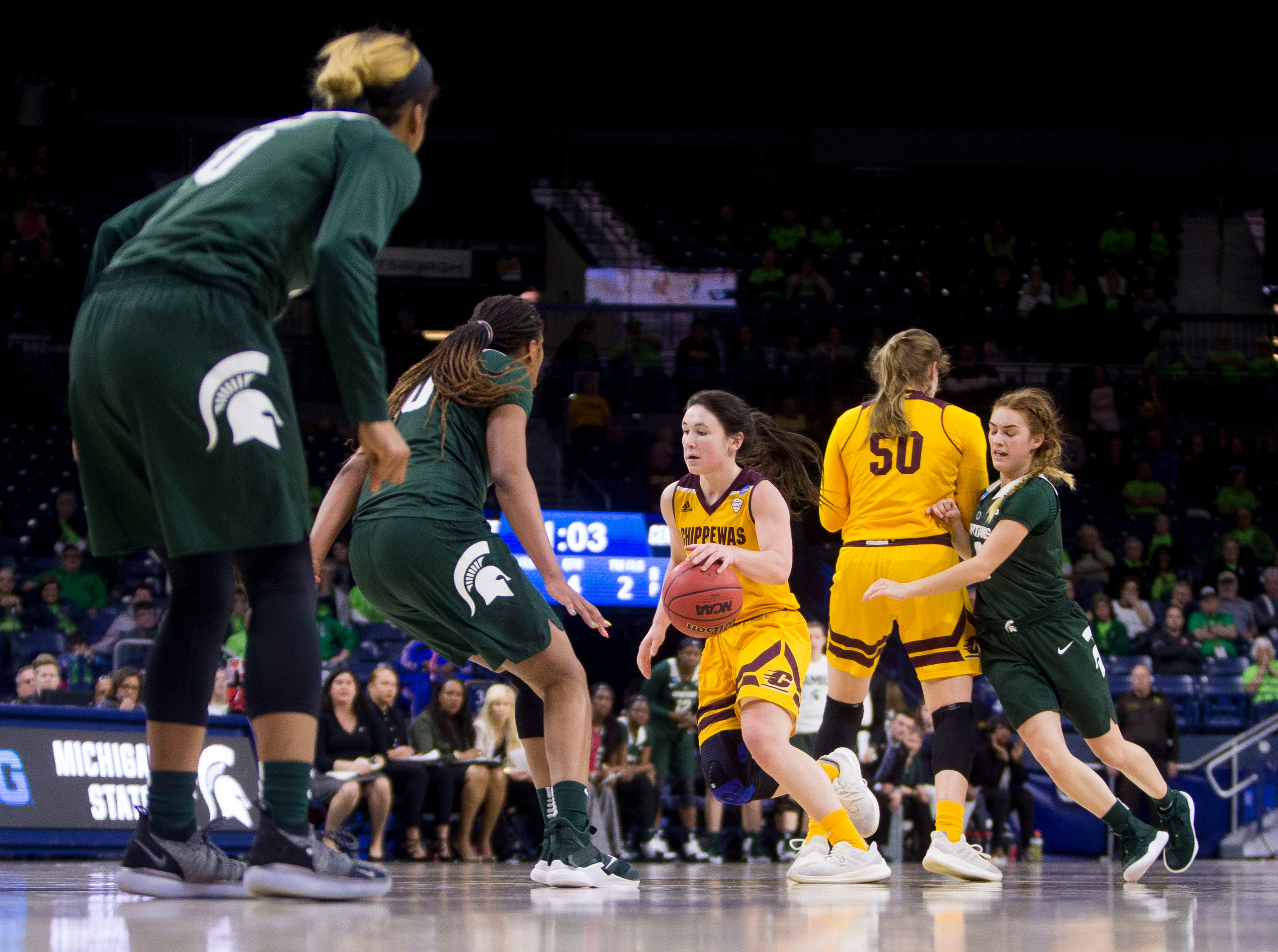 Central Michigan's Presley Hudson, center, drives in as Michigan State's Sidney Cooks (10) defends during a first-round game in the NCAA women's college basketball tournament in South Bend, Ind., Saturday, March 23, 2019. Michigan State won 88-87.