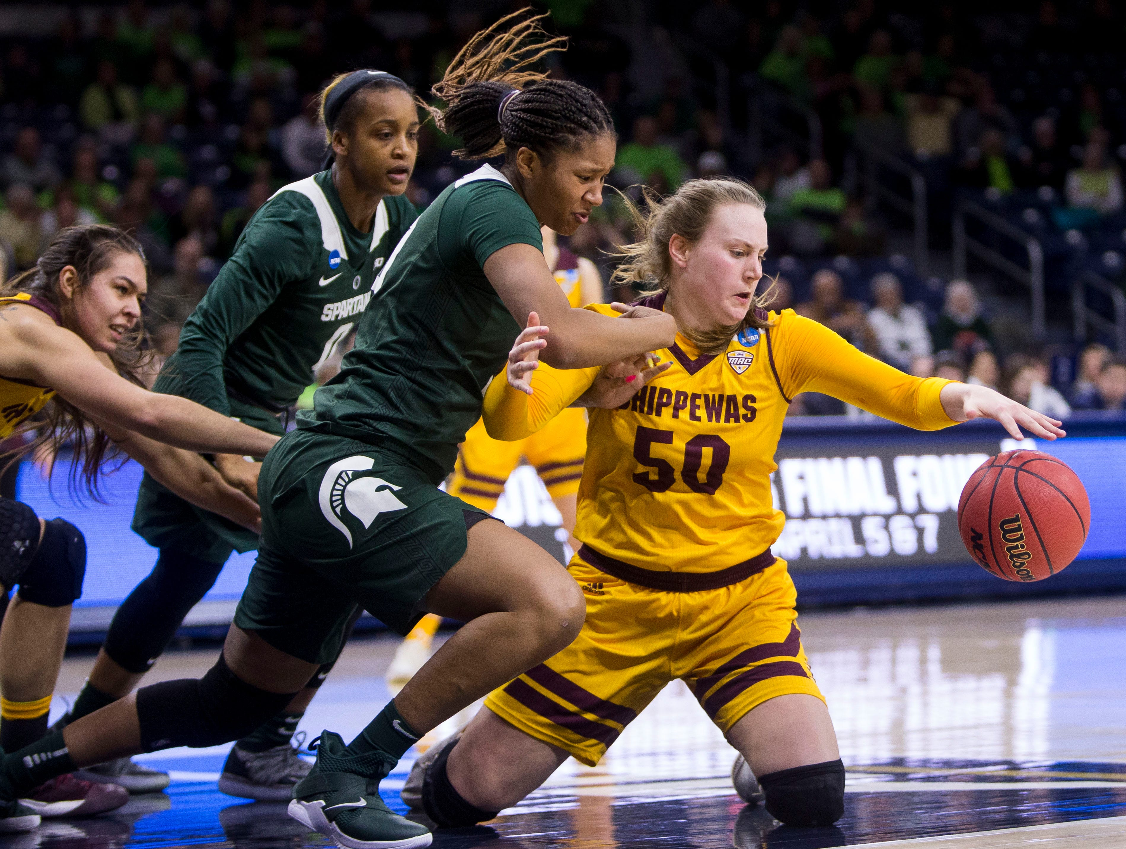 Central Michigan's Kyra Bussell (50) competes for a loose ball with Michigan State's Sidney Cooks (10) during a first-round game in the NCAA women's college basketball tournament in South Bend, Ind., Saturday, March 23, 2019. Michigan State won 88-87.