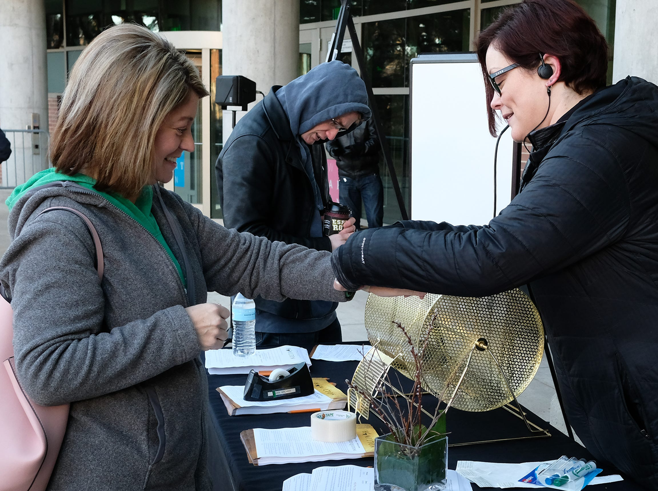 Dawn Ellis from East Lansing, left, gets a wristband with a number on it from Lisa Rentz, Director of Marketing and Communication at the Wharton Center Saturday, March 23, 2019. The wristband makes them eligible to purchase tickets for Hamilton the Broadway Musical.