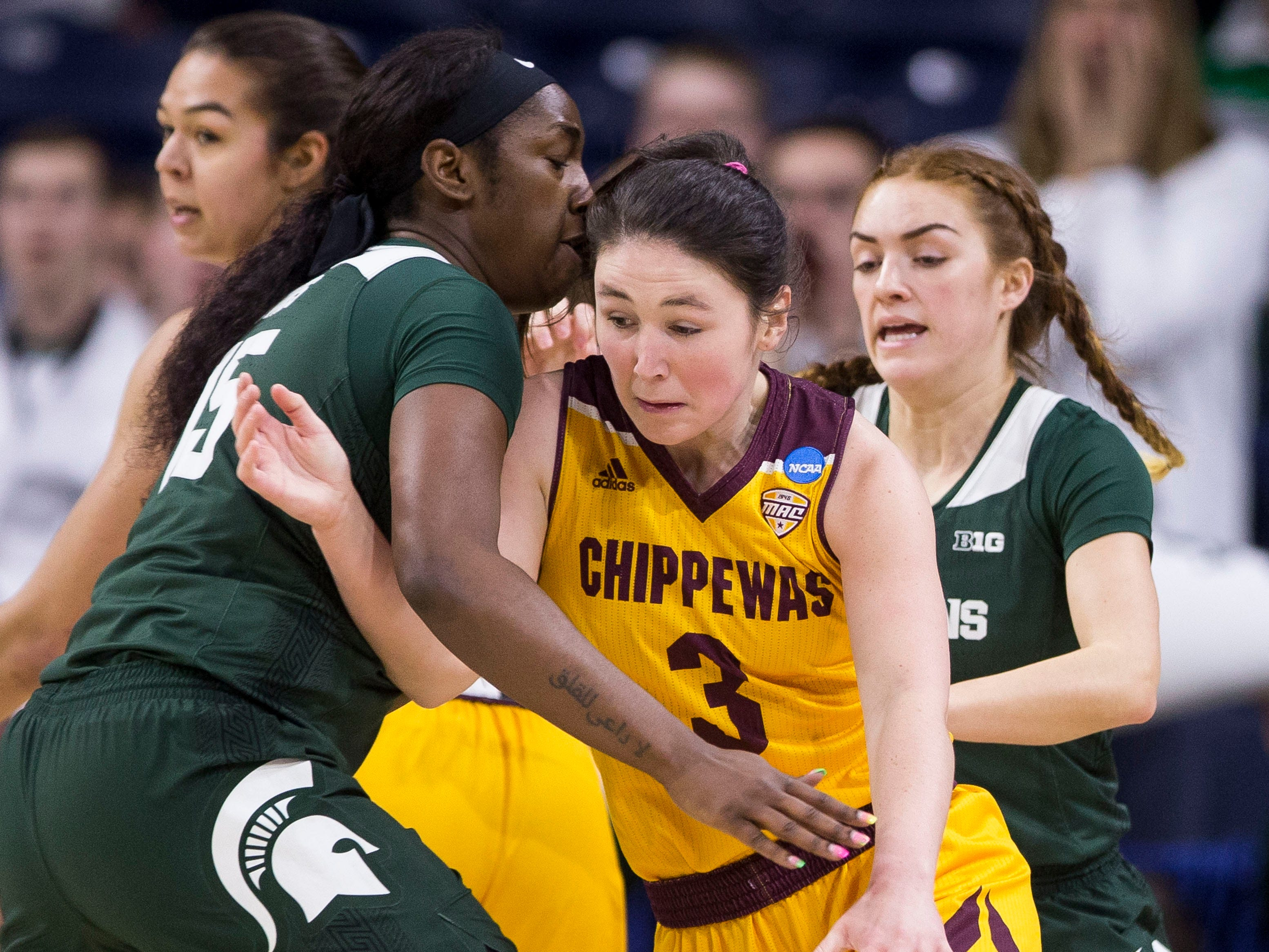 Central Michigan's Presley Hudson (3) moves between Michigan State's Victoria Gaines, left, and Taryn McCutcheon during a first-round game in the NCAA women's college basketball tournament in South Bend, Ind., Saturday, March 23, 2019. (AP Photo/Robert Franklin)