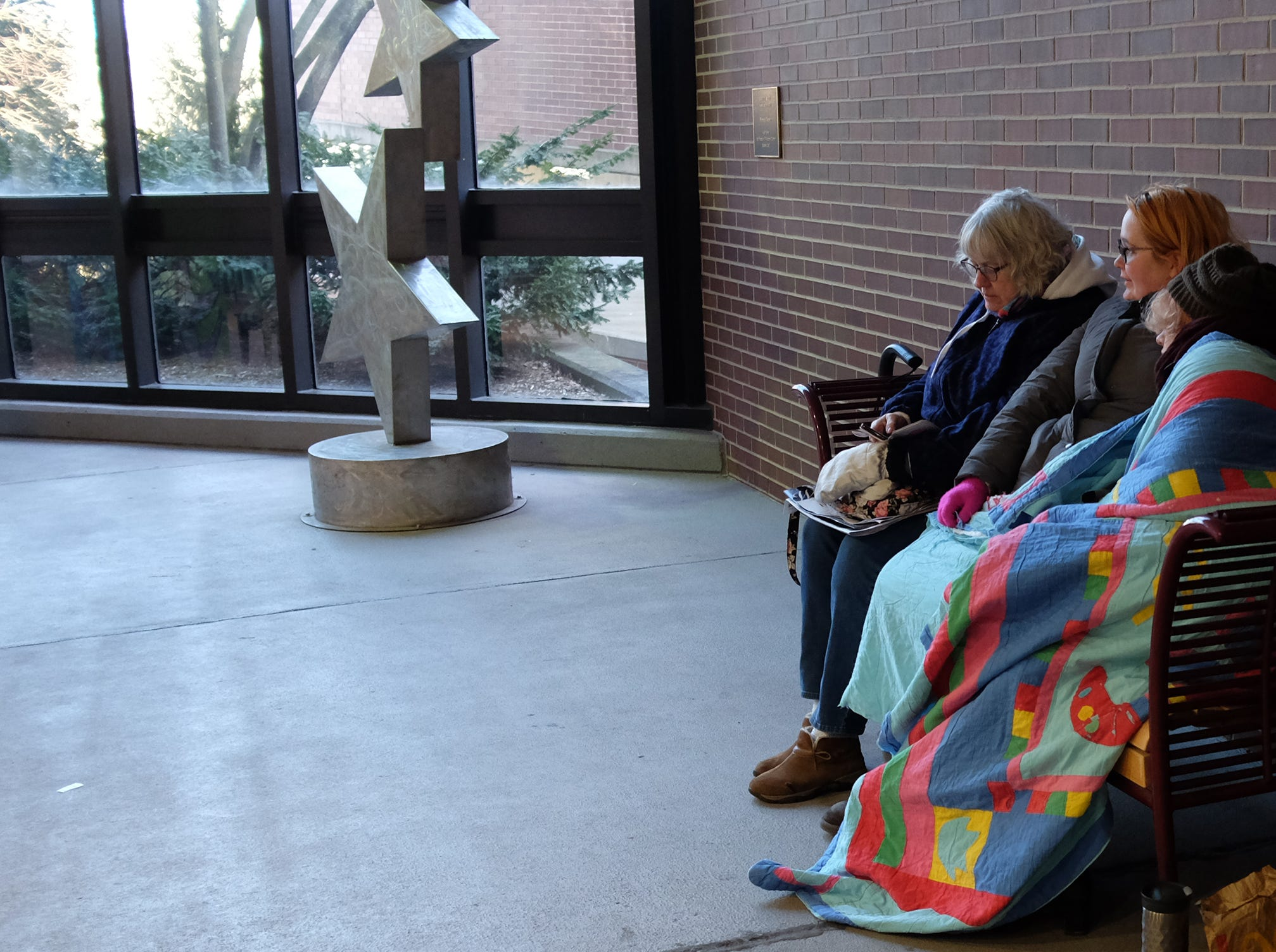 """People try to stay warm as they wait for the opportunity to buy """"Hamilton"""" tickets that went on sale at the Wharton Center Saturday, March, 23, 2019."""
