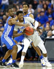 Memphis Tigers guard Alex Lomax (2) and  guard Jeremiah Martin (3) apply defensive pressure to Creighton Bluejays guard Kaleb Alejandro Joseph (14) during their second round NIT game Friday, March 22 , 2019, in Omaha, Neb.