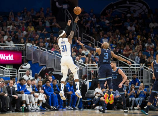 Orlando Magic guard Terrence Ross (31) hits a 3-pointer over Memphis Grizzlies guard Jevon Carter (3) during the first half of an NBA basketball game in Orlando, Fla., Friday, March 22, 2019. (AP Photo/Willie J. Allen Jr.)