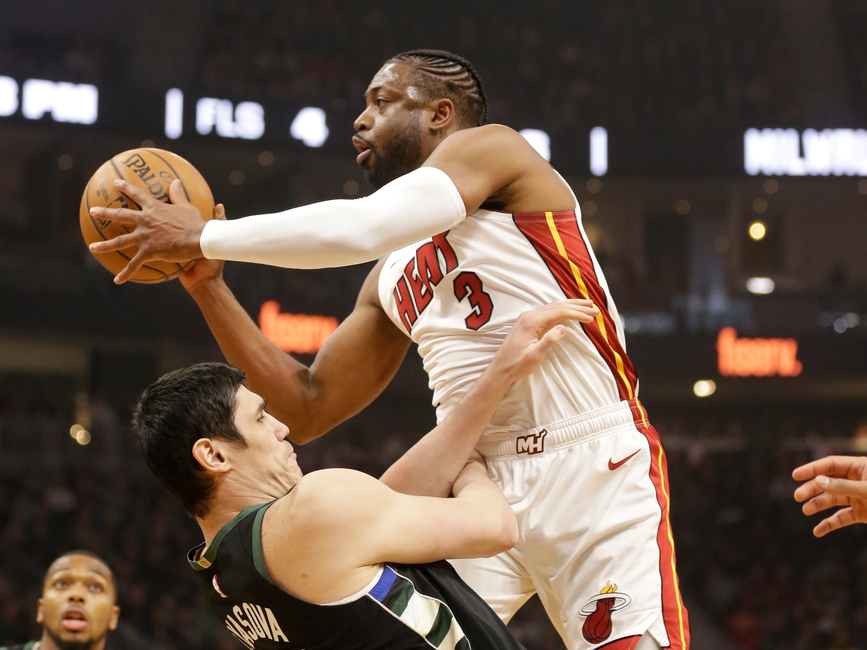 Heat guard Dwyane Wade is fouled by the Bucks' Ersan Ilyasova on a drive to the rack during the first half.