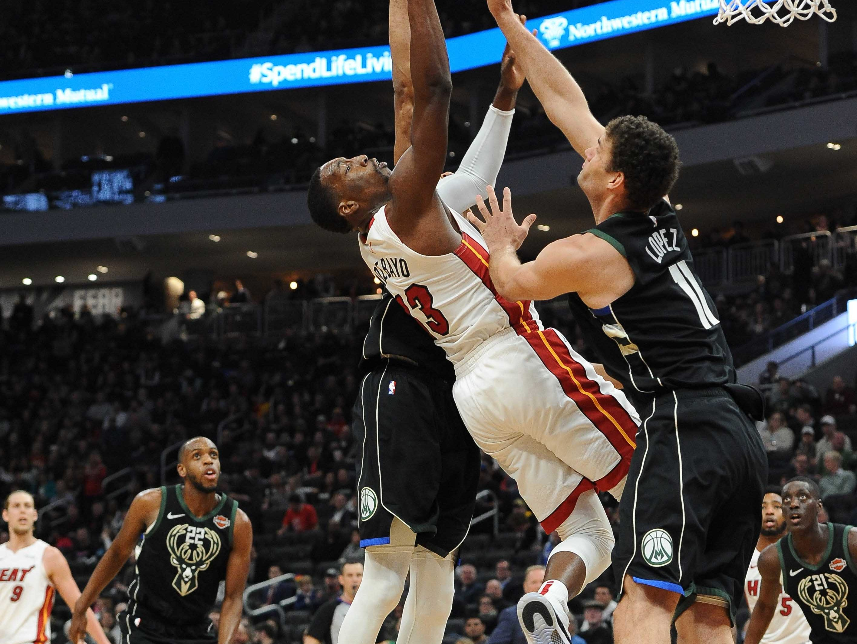 Heat center Bam Adebayo is fouled as he goes to the basket against Brook Lopez (right) and Giannis Antetokoumpo of the Bucks during the third quarter.