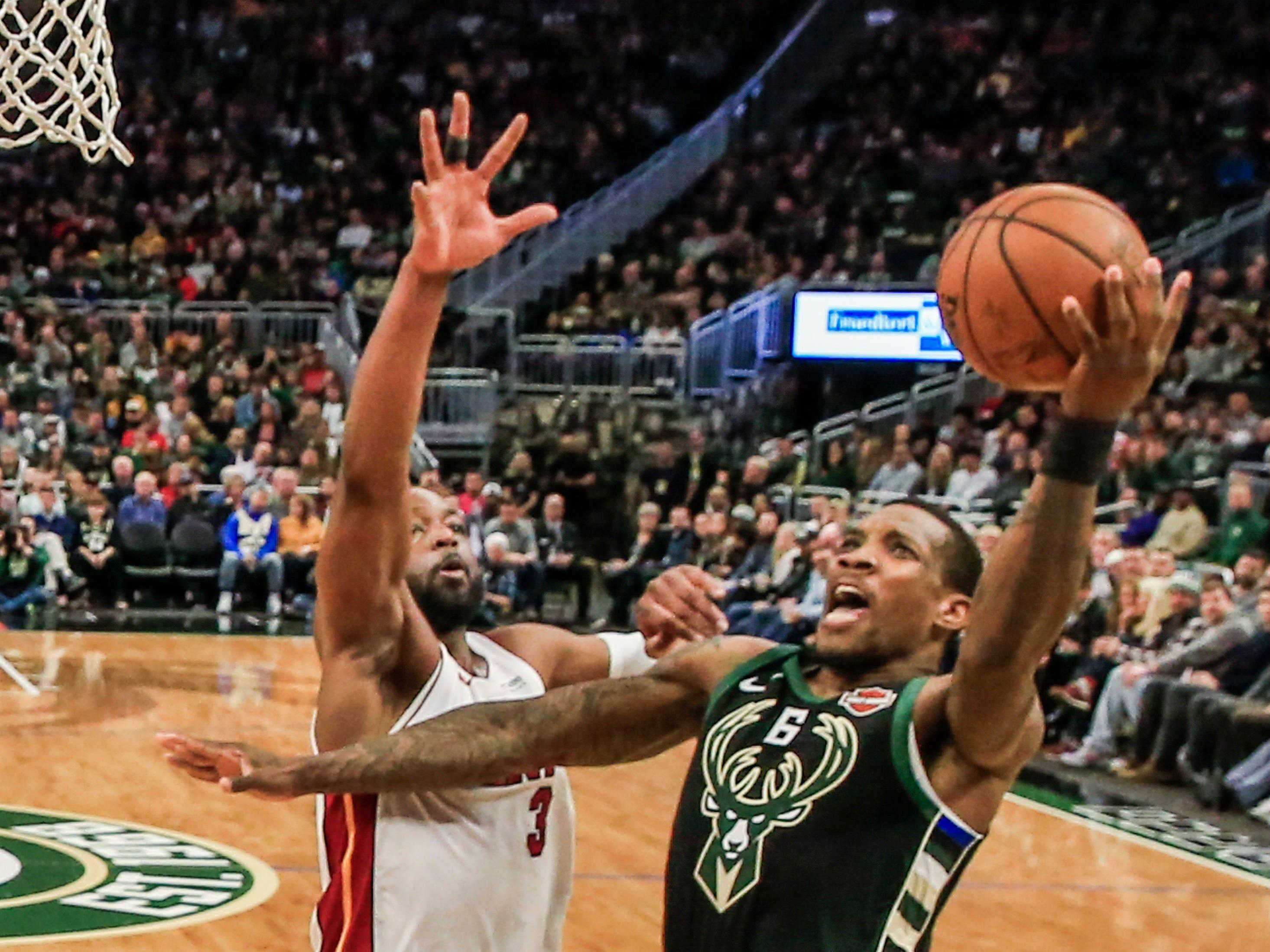 Bucks guard Eric Bledsoe gets past Heat Dwyane Wade for a basket Friday night.