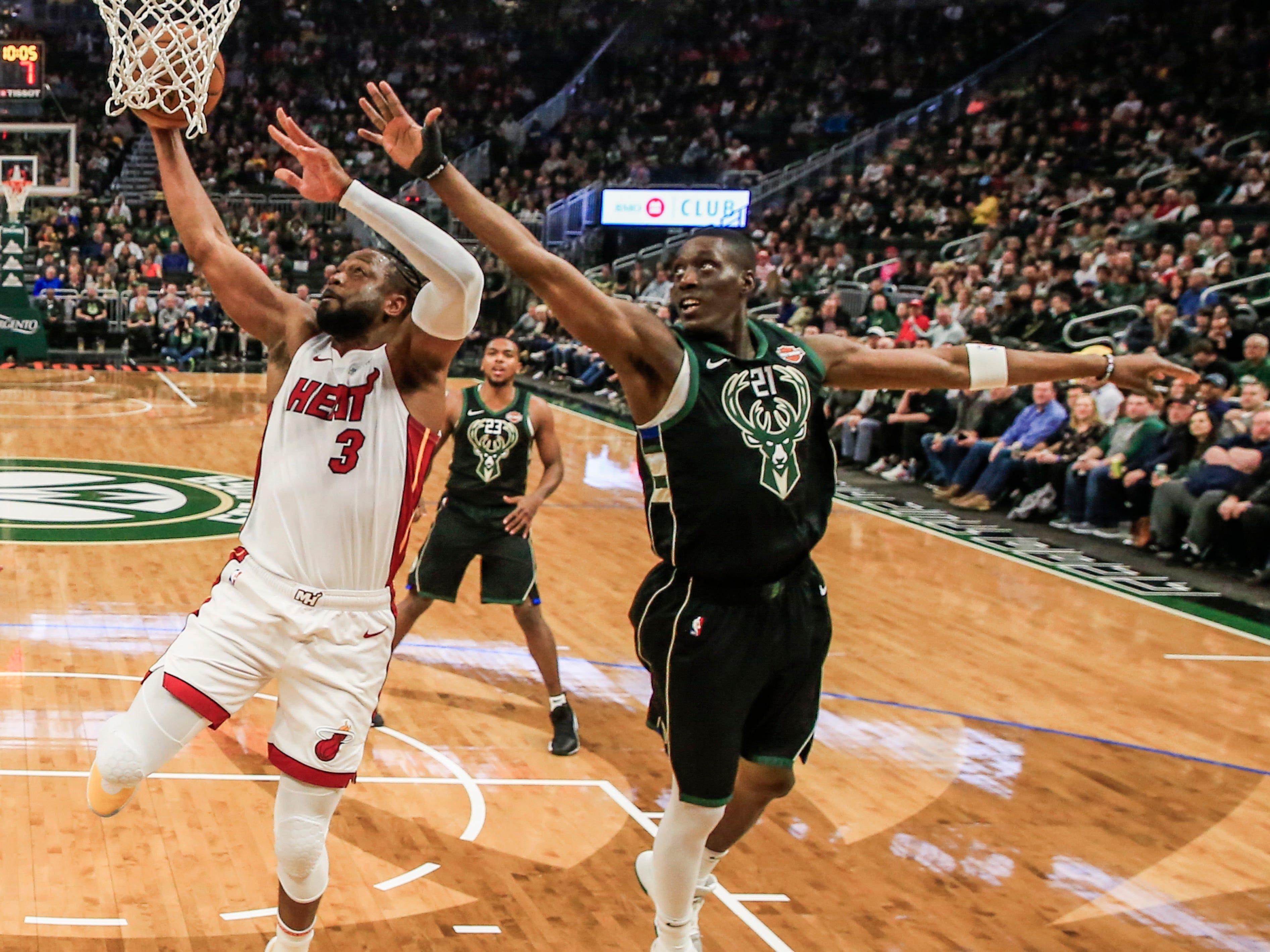 Heat guard Dwyane Wade beats Bucks guard Tony Snell to the basket for a layup Friday night.
