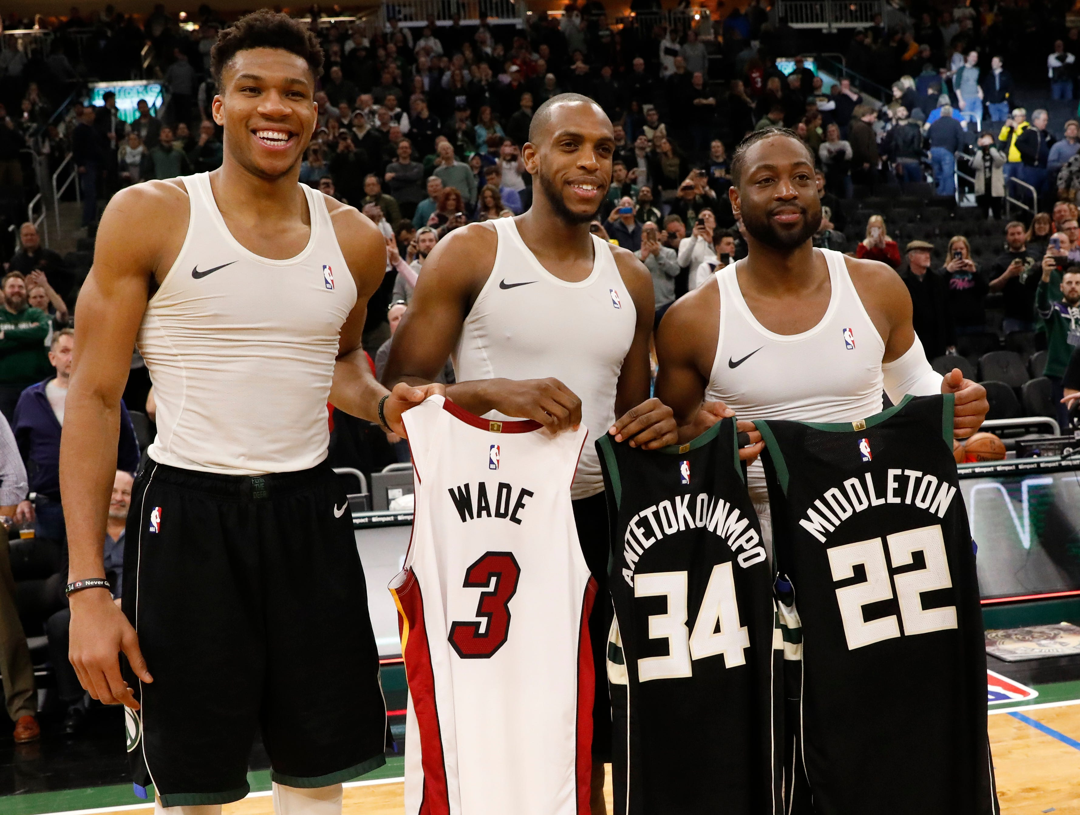 Giannis Antetokounmpo and Khris Middleton of the Bucks swap jerseys with former Marquette star Dwyane Wade. The Heat star is retiring after this season and was playing his final regular-season game in Milwaukee on Friday night.