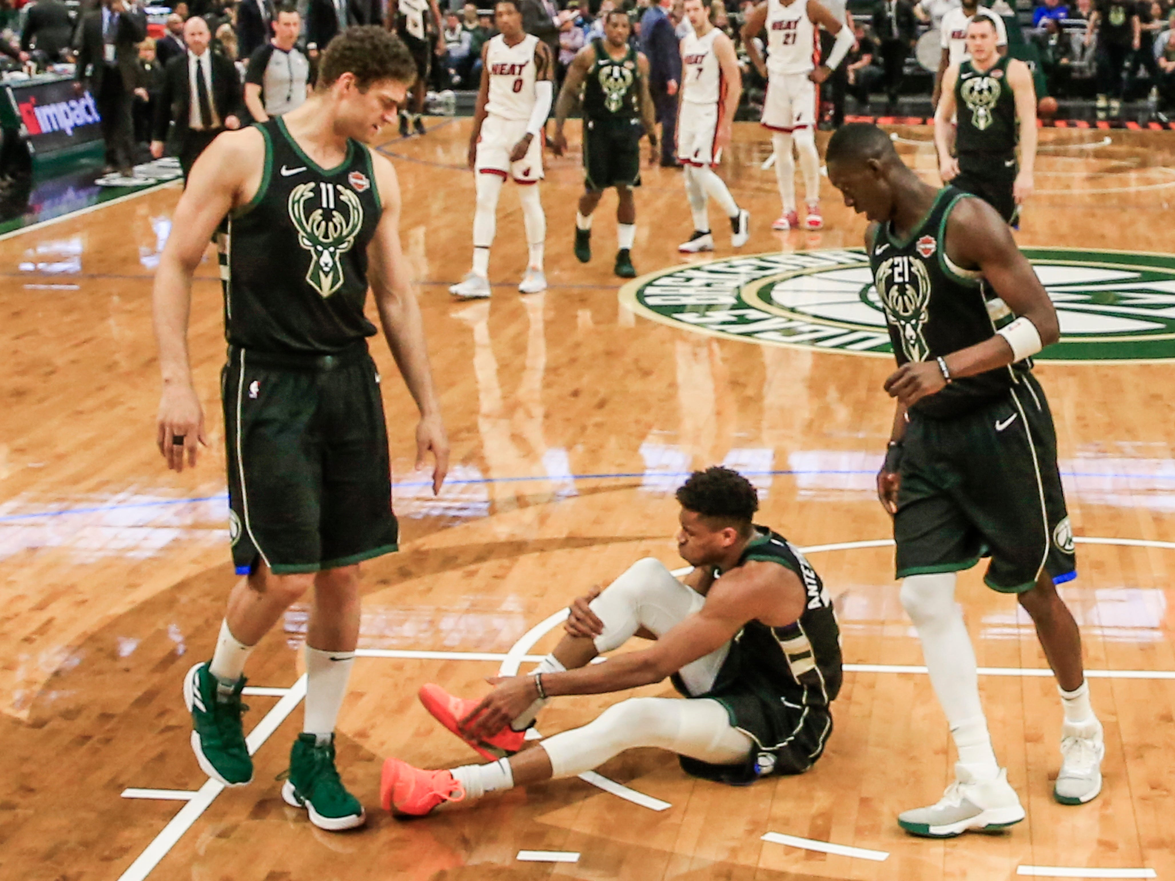 Bucks forward Giannis Antetokounmpo sits on the floor holding his leg after rolling his right ankle as teammates Brook Lopez (left) and Tony Snell come to check on him during the first half.