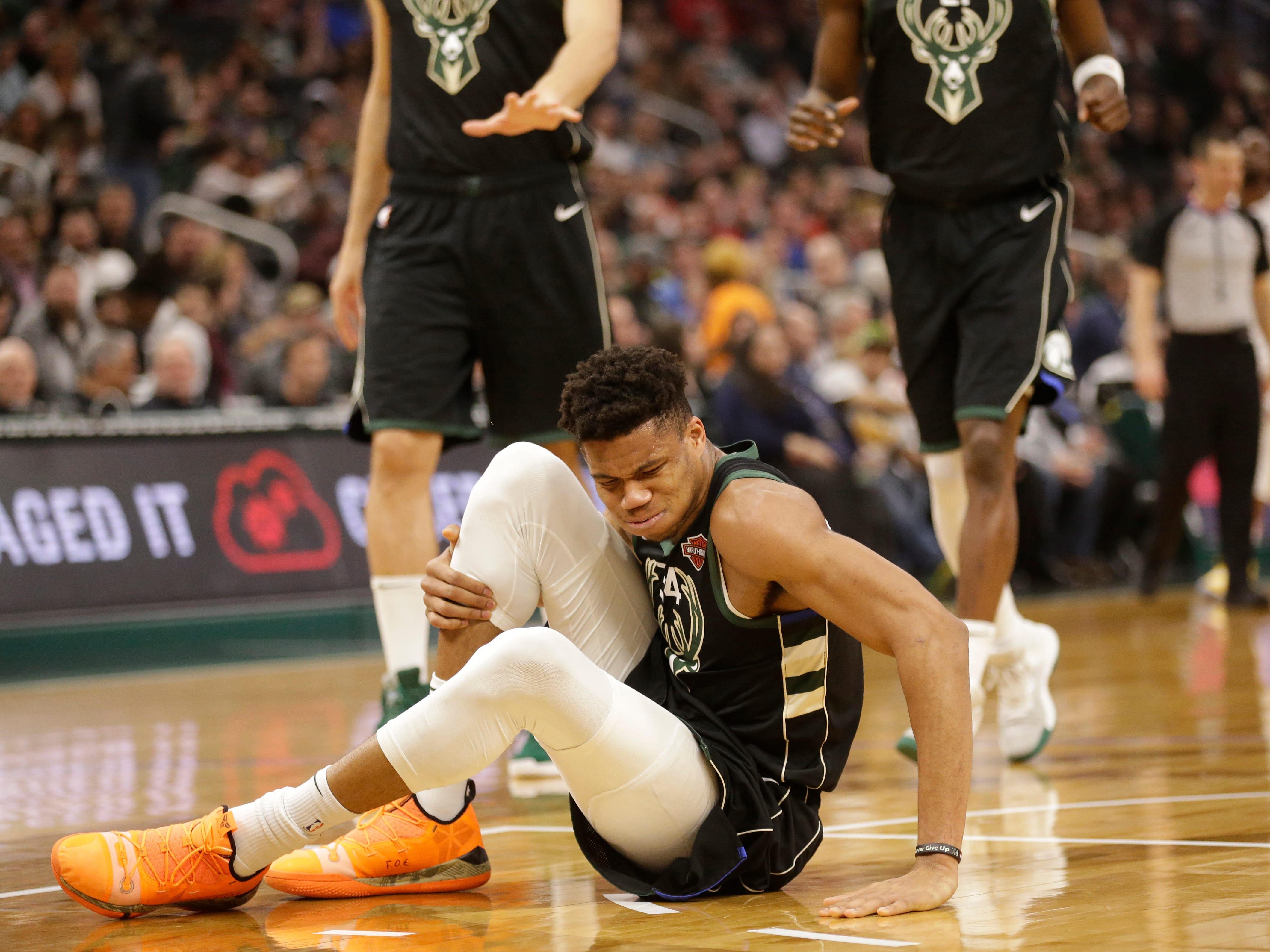 Bucks star Giannis Antetokounmpo sits on the court in some pain after rolling his right ankle during the first half.