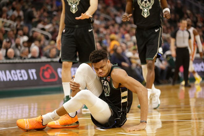 Bucks star Giannis Antetokounmpo sits on the court in some pain after rolling his right ankle in a recent game.