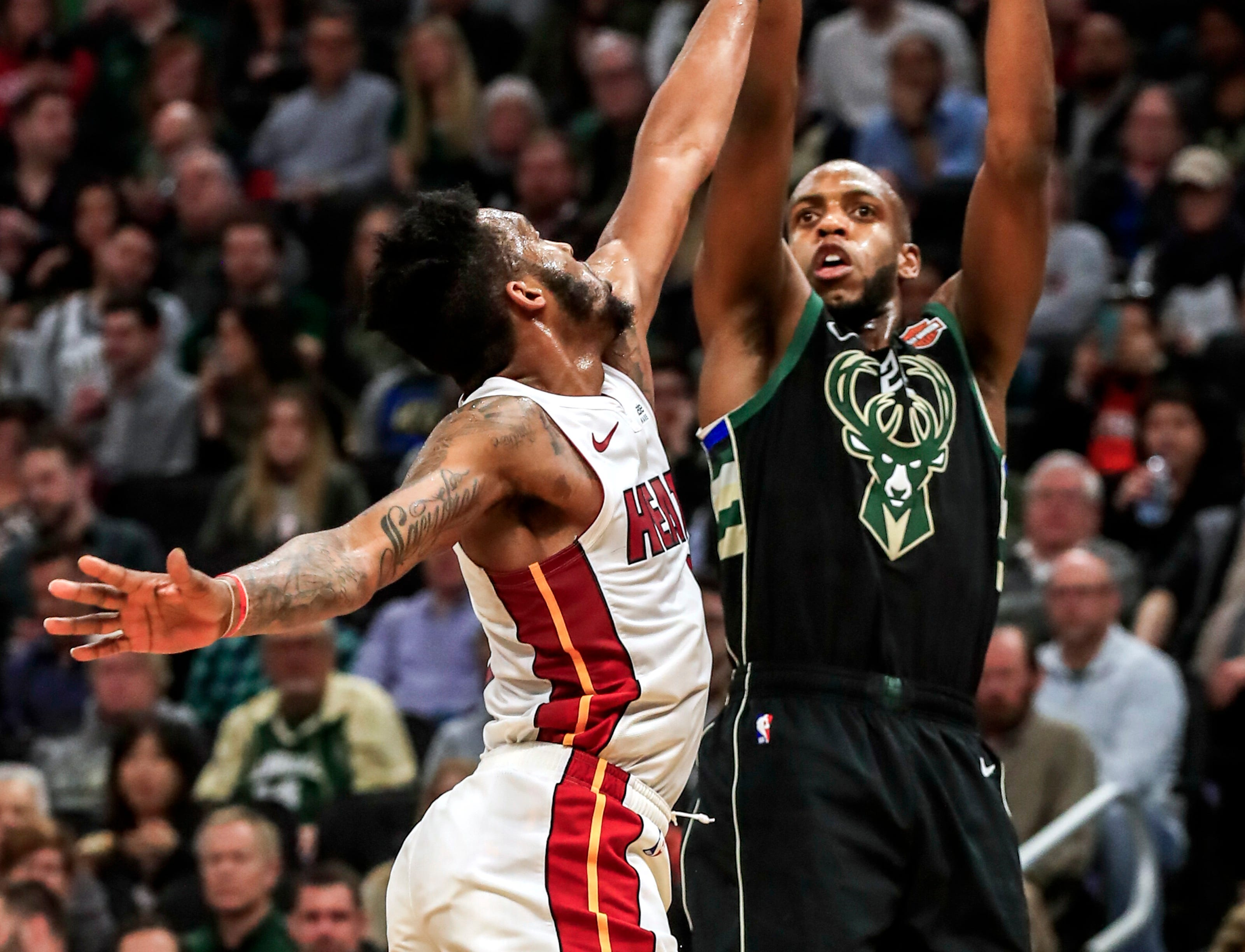 Bucks forward Khris Middleton hoists a a shot up over Heat forward Derrick Jones Jr. on Friday night. Middleton just missed a triple-double, finishing with 18 points, 10 assists and eight boards.
